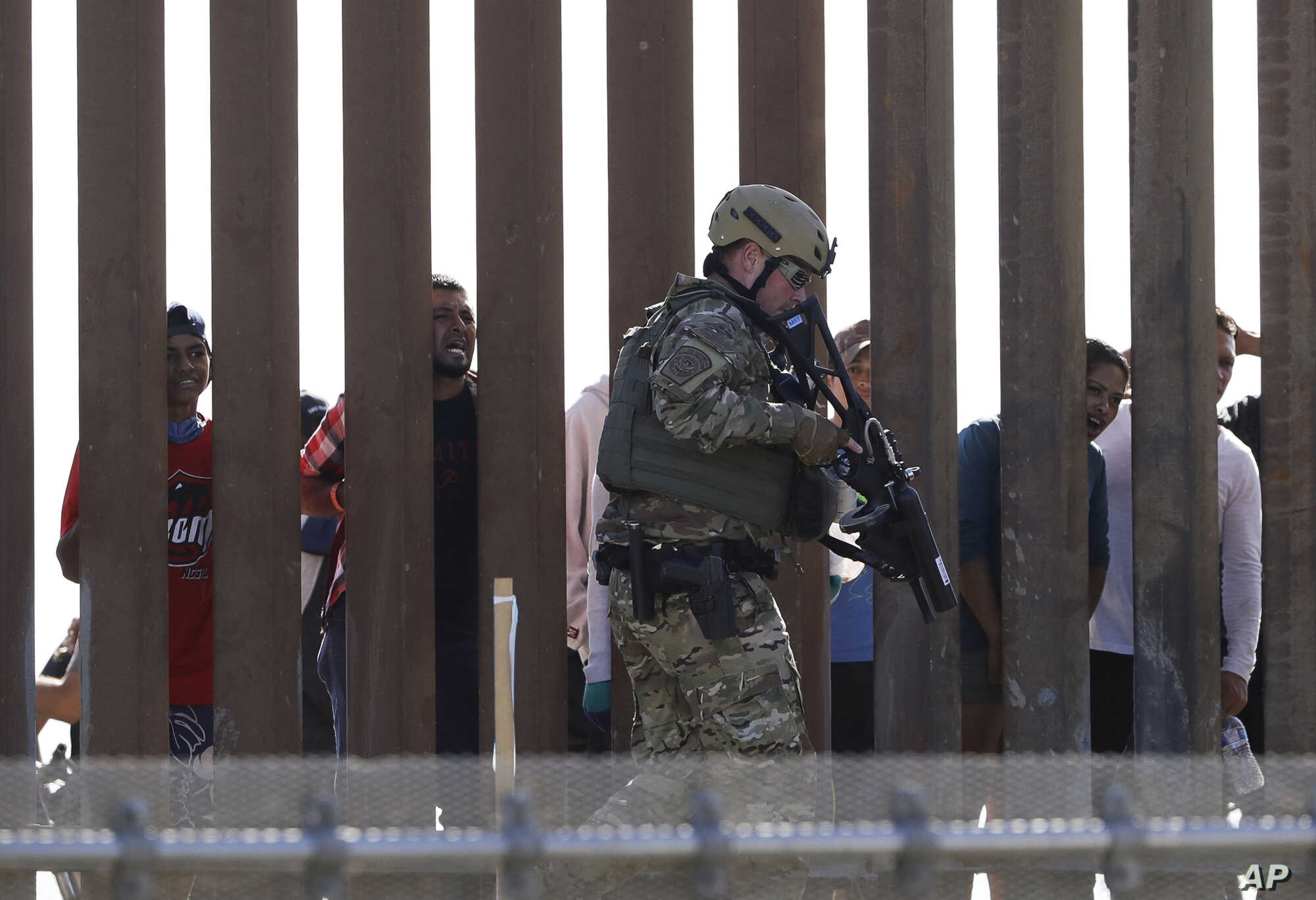 A U.S. Customs and Border Protection officer walks along a wall at the border between Mexico and the United States, as seen from San Diego, California, Nov. 25, 2018.