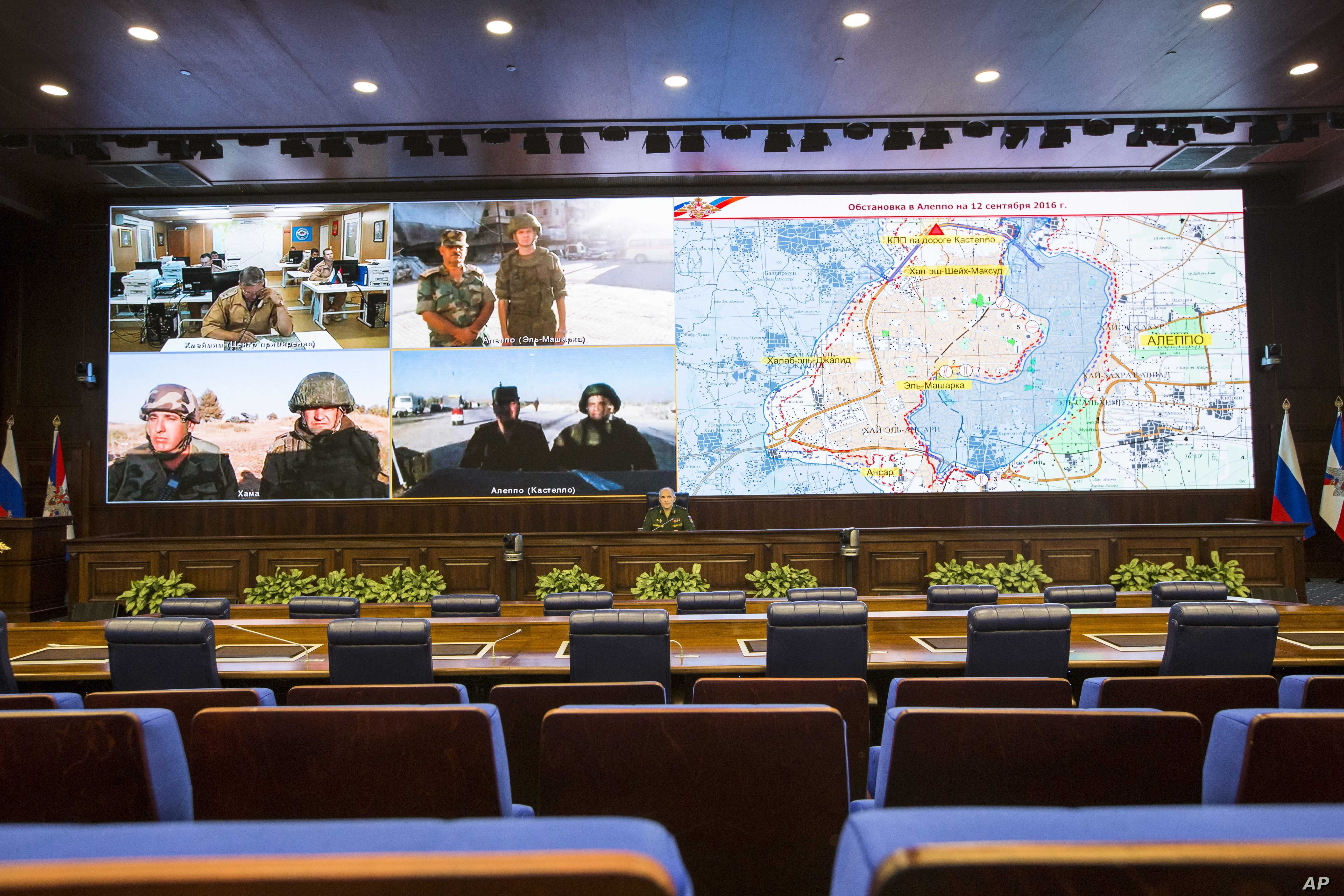 Lt.-Gen. Sergei Rudskoi, center, of the Russian Military General Staff listens to Russian and Syrian officers during a video call, as a Syrian army facility is displayed on screen, at a Russian Defense Ministry building in Moscow, Russia, Sept. 12, 2...