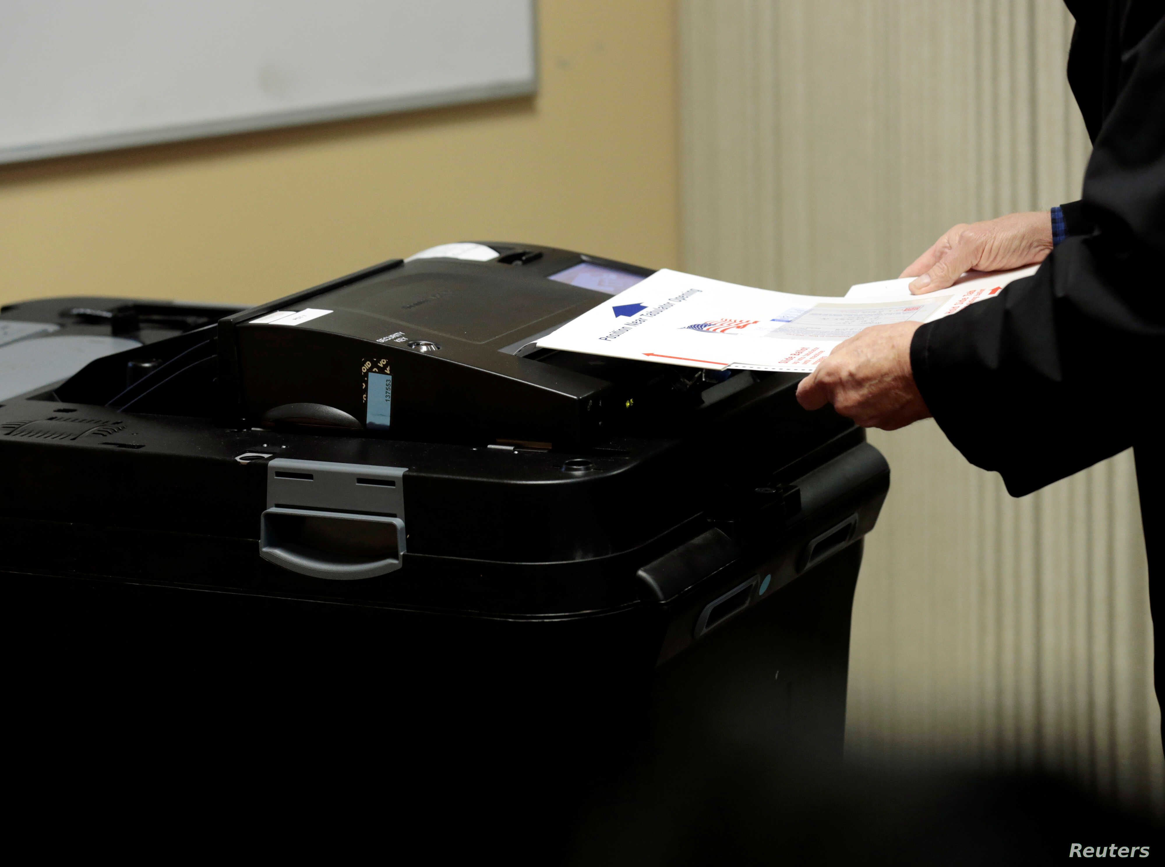 A person places his ballot in a tabulating machine as they vote in midterm election at the St. Paul Lutheran Church in East Lansing, Michigan, Nov. 6, 2018.