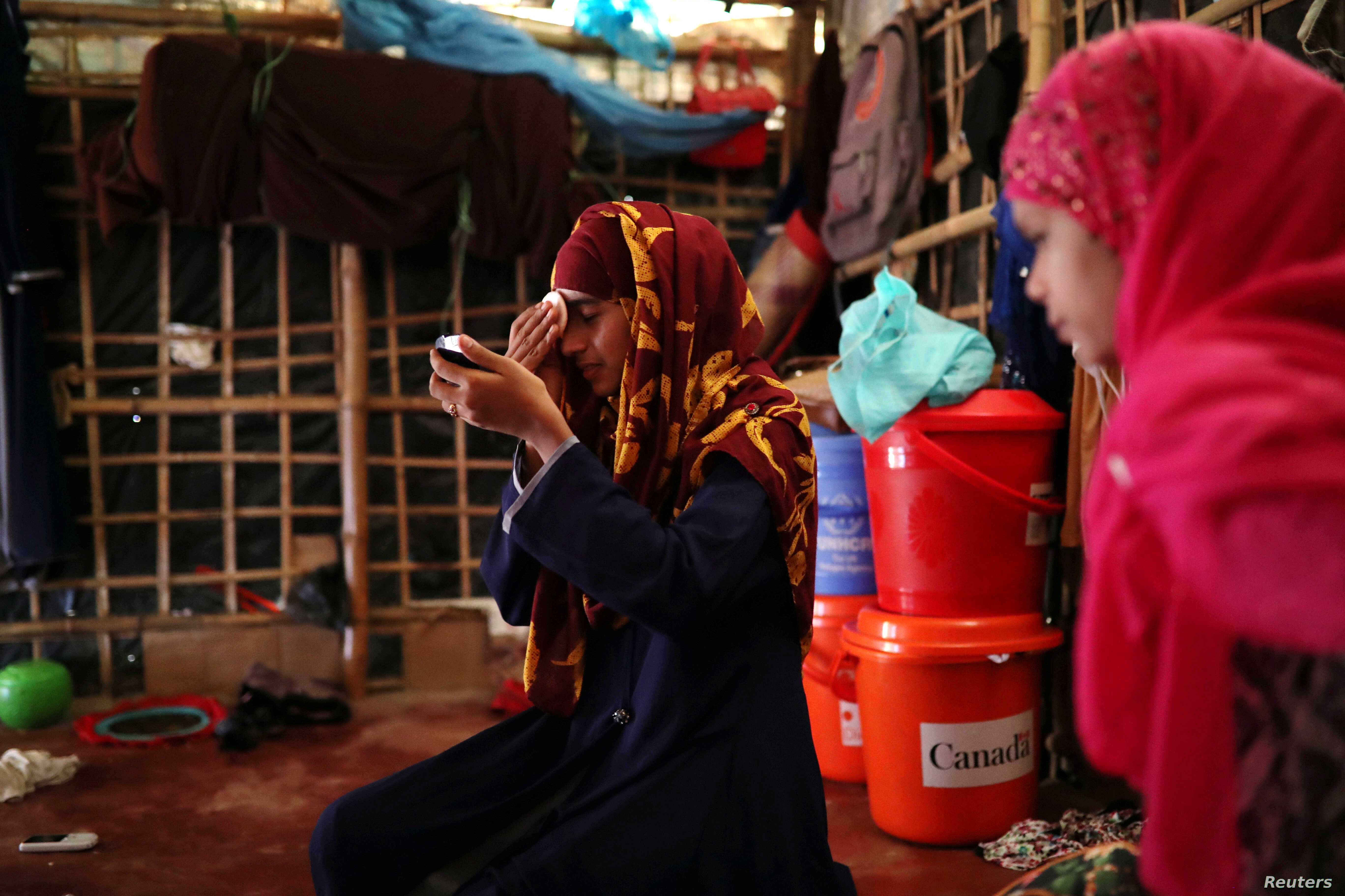 Formin Akter applies makeup before heading to Chittagong to attend school at the Asian University for Women in Cox's Bazar, Bangladesh, Aug. 24, 2018.
