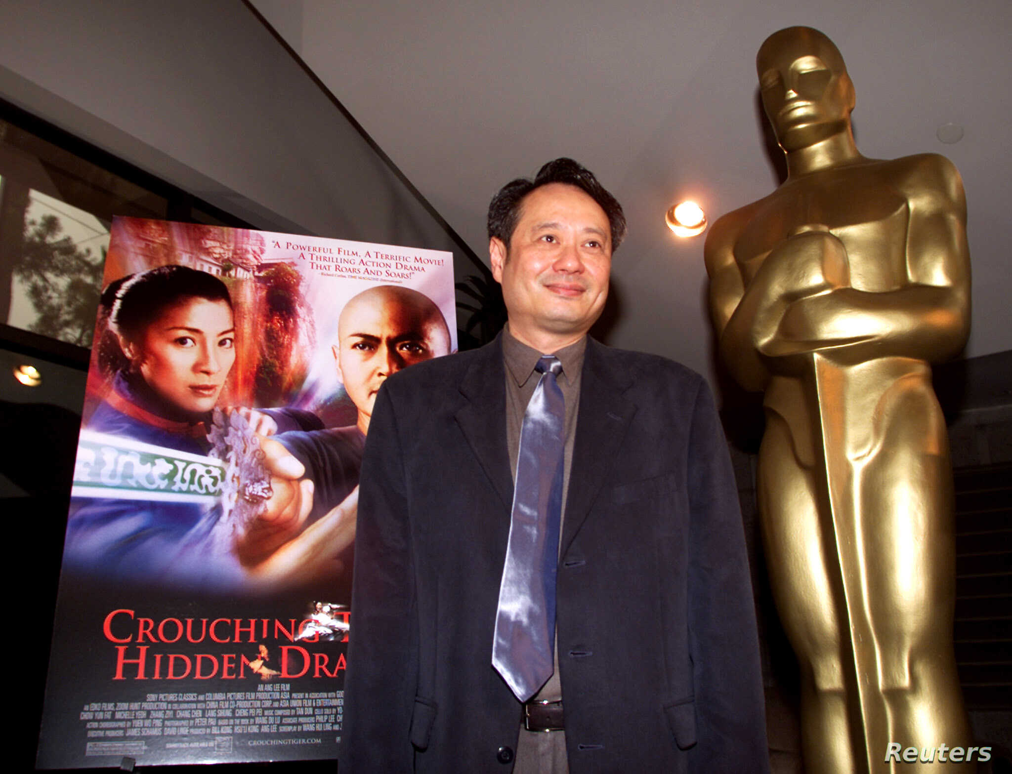 """FILE - Director Ang Lee stands next to the movie poster for his Academy Award-nominated film, """"Crouching Tiger, Hidden Dragon,"""" at the Academy of Motion Pictures of Arts and Sciences in Beverly Hills, March 23, 2001."""