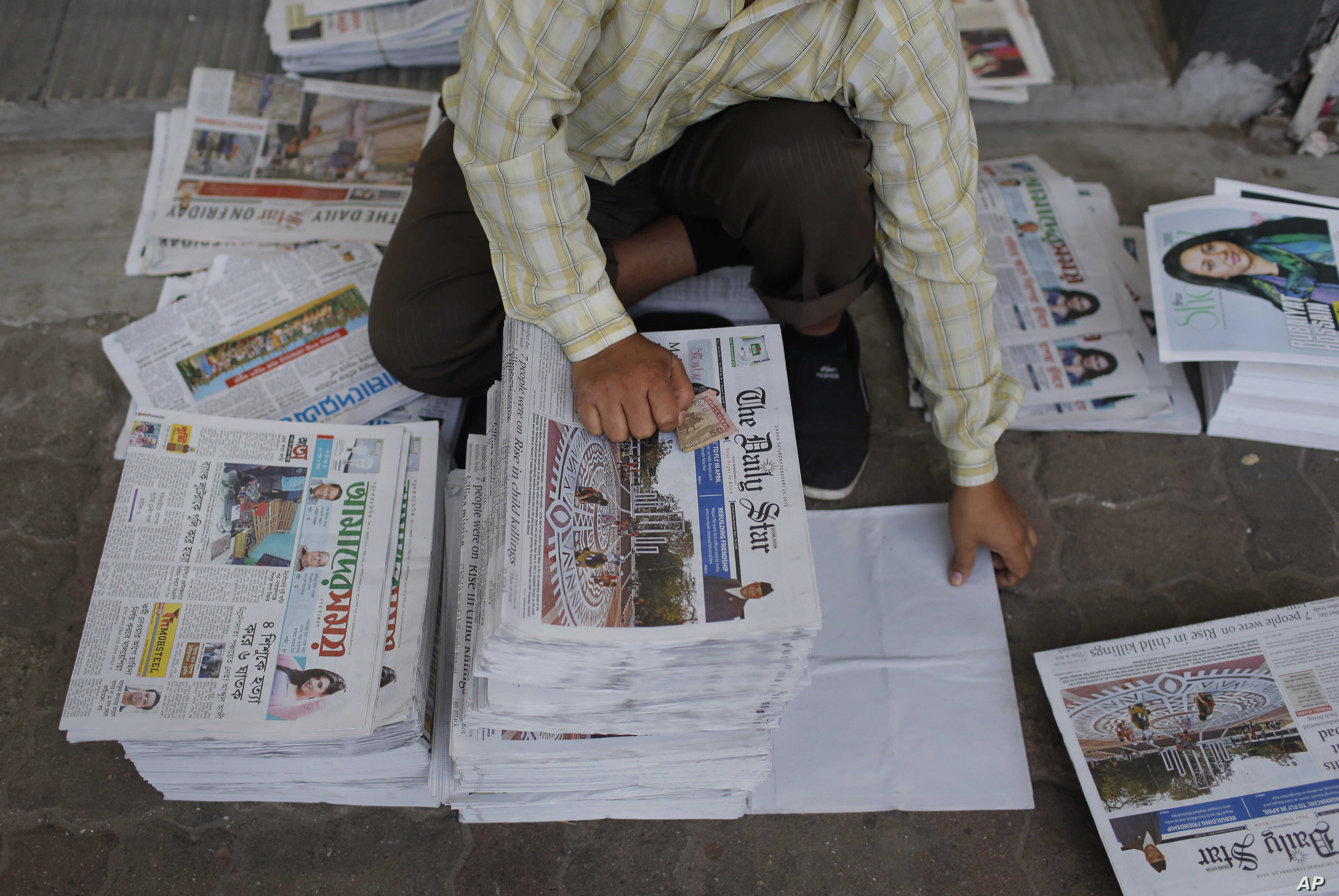 FILE - A Bangladeshi worker classifies newspapers, in Dhaka, Bangladesh, Feb. 20, 2016. Under  Section 57 of Bangladesh's Information and Communications Technology Act, journalists can be jailed for a variety of offenses, such as defamation, hurtin...