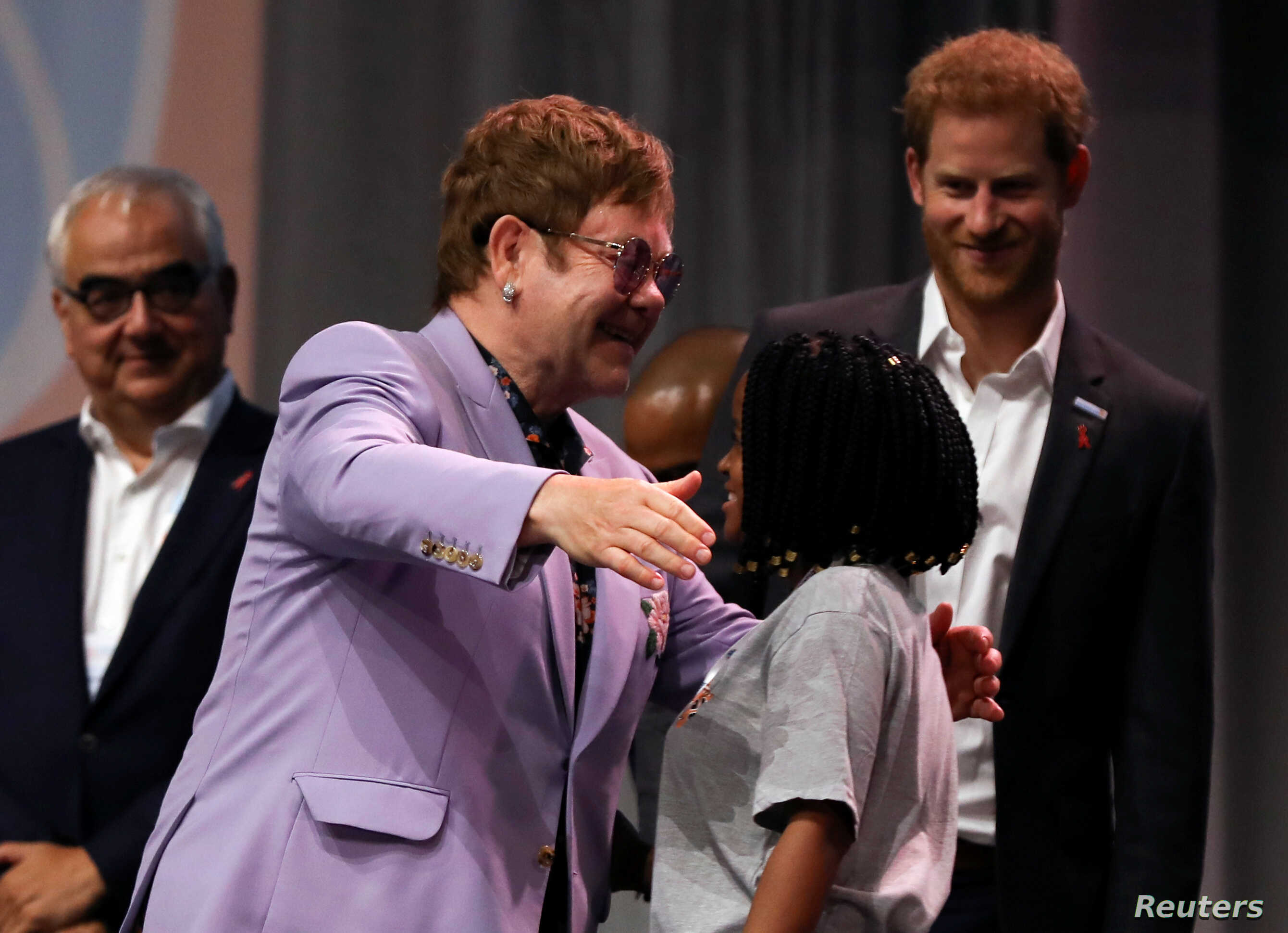 """British musician Elton John embraces a participant as Britain's Prince Harry looks on during a panel """"Breaking barriers of inequity in the HIV response"""" during the 22nd International AIDS Conference (AIDS 2018), the largest HIV/AIDS-focused meeting i..."""