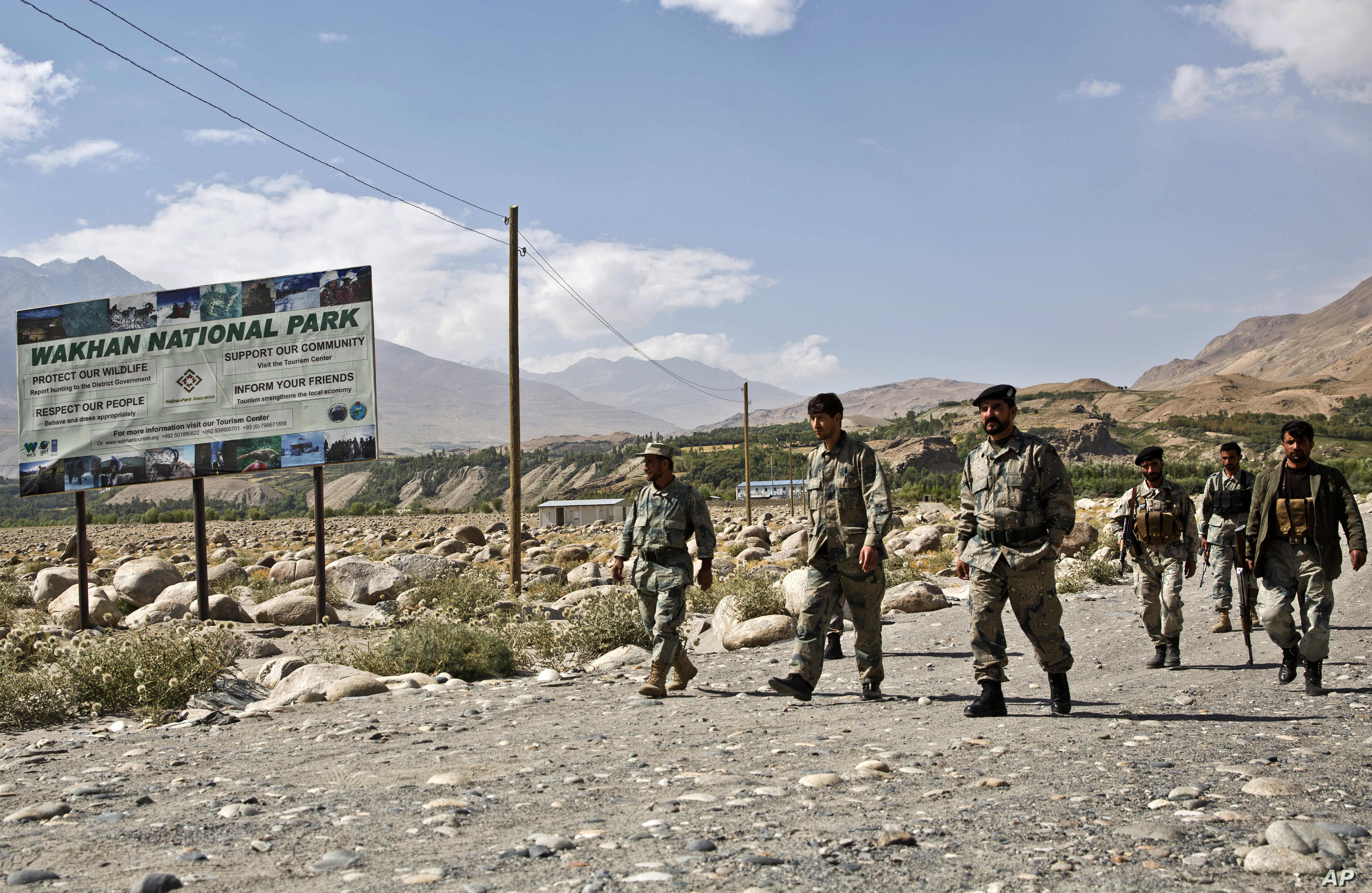 FILE - Afghan border police walk the Afghanistan side of the border with Tajikistan, in Ishkashim, Badakhshan province, far northeastern Afghanistan, Aug. 16, 2016.