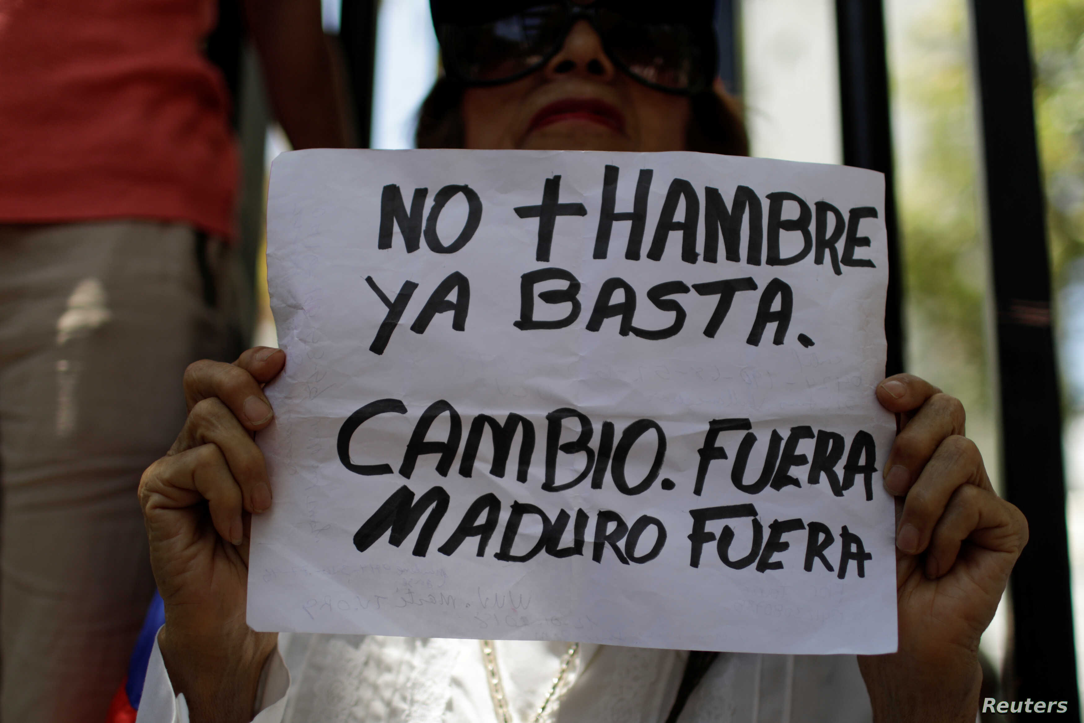 """A woman holds a placard that reads """"No more hunger. Stop. Change. Out Maduro Out"""" — a reference to President Nicolas Maduro — during a gathering of opposition supporters in Caracas, Venezuela, March 17, 2018."""