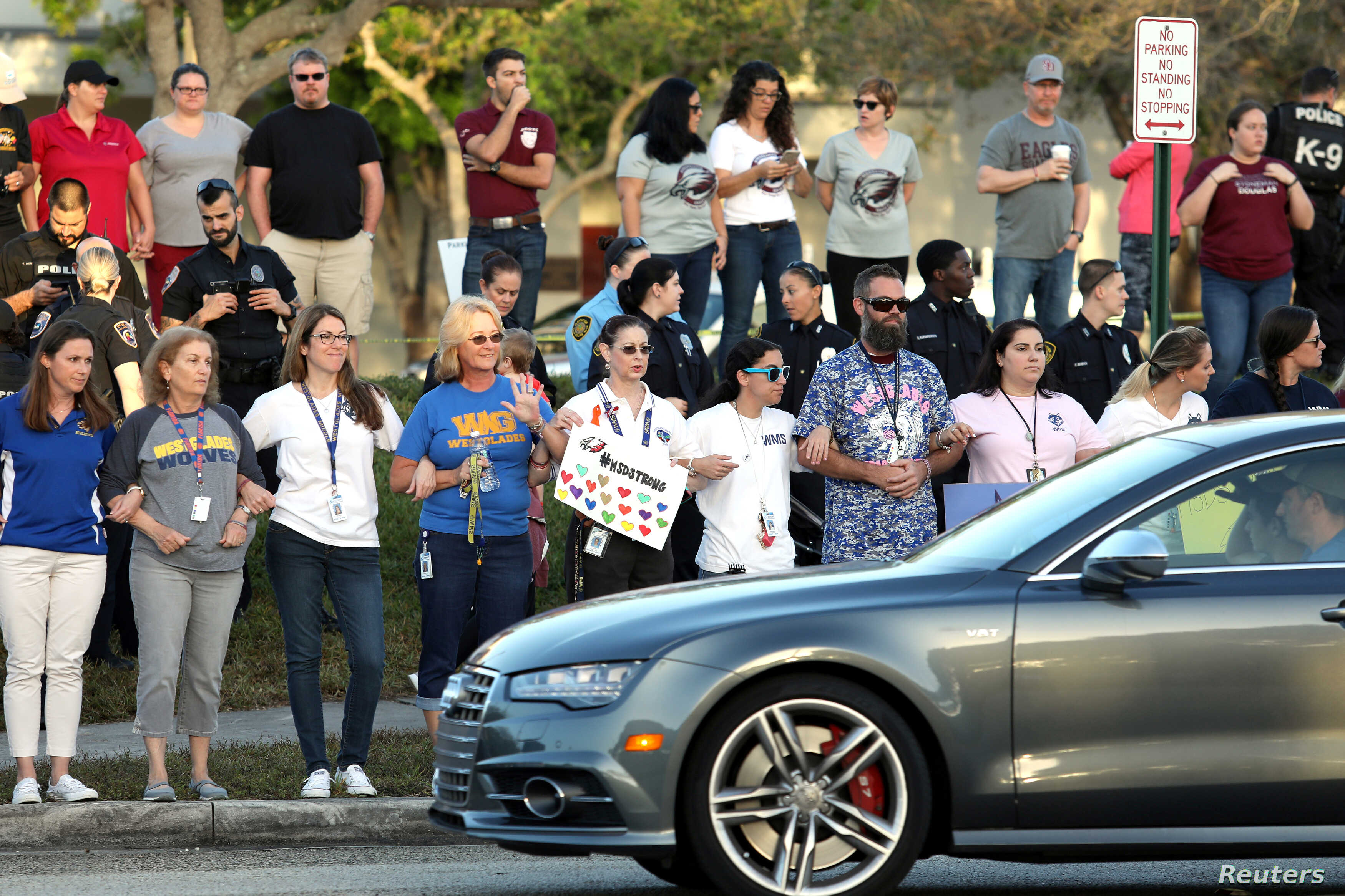 Local residents show their support as students arrive at Marjory Stoneman Douglas High School for the first time since the mass shooting in Parkland, Florida, Feb. 28, 2018.