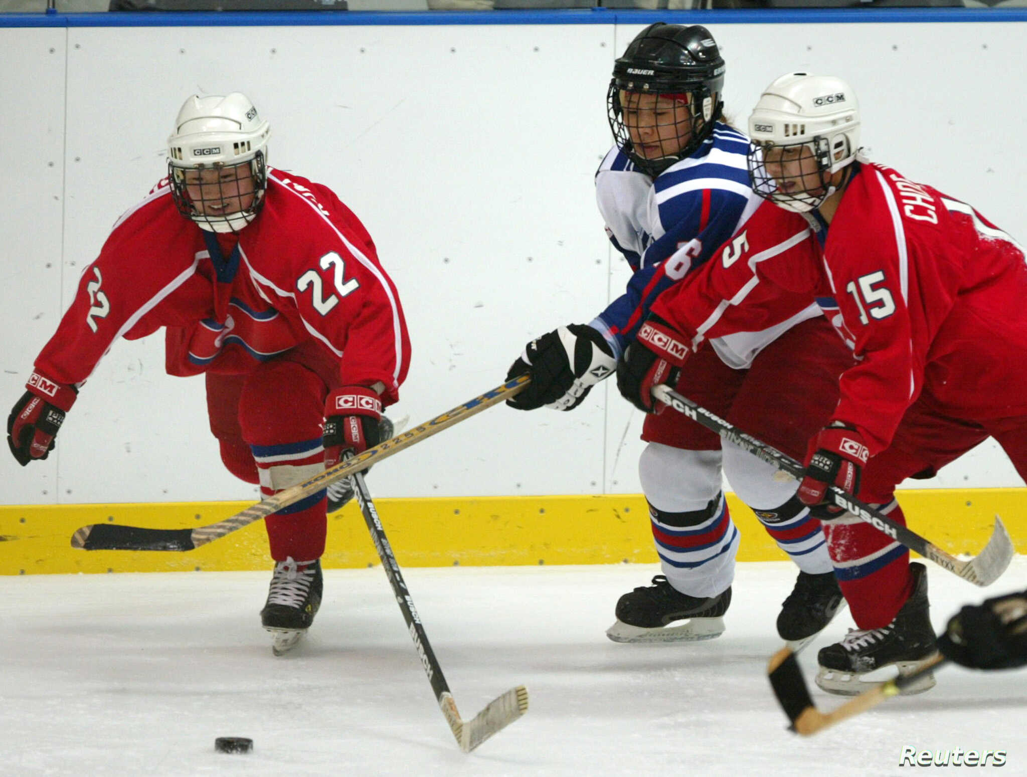 FILE - A South Korean player (white jersey) struggles for the puck during a women's ice hockey match at the fifth Winter Asian Games in Misawa, Japan Feb. 3, 2003.