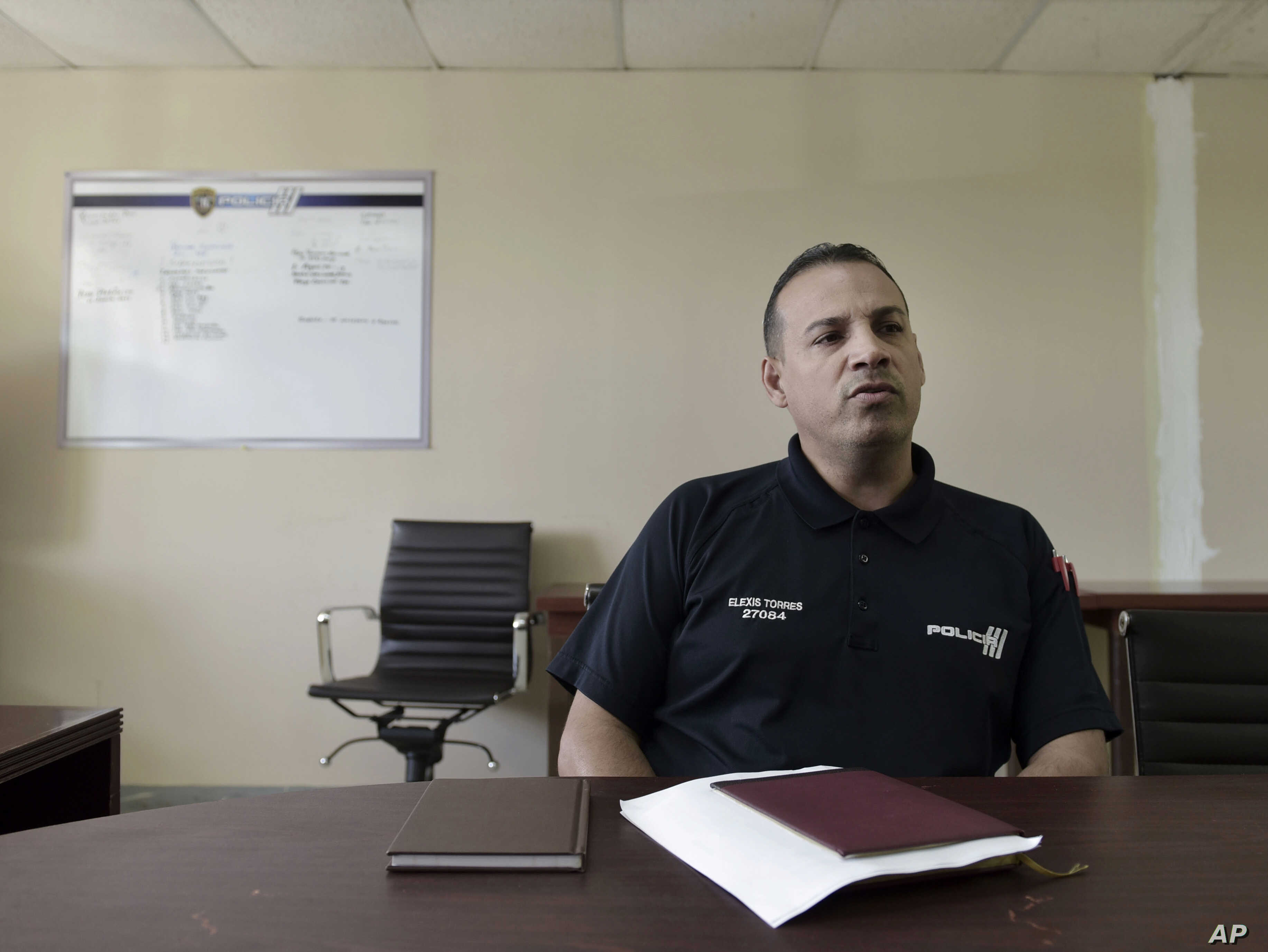 In this Jan. 9, 2018 photo, inspector Elexis Torres, is interviewed in Carolina, Puerto Rico. Torres heads a unit that is investigating eight homicides in a jurisdiction that includes the working-class city.