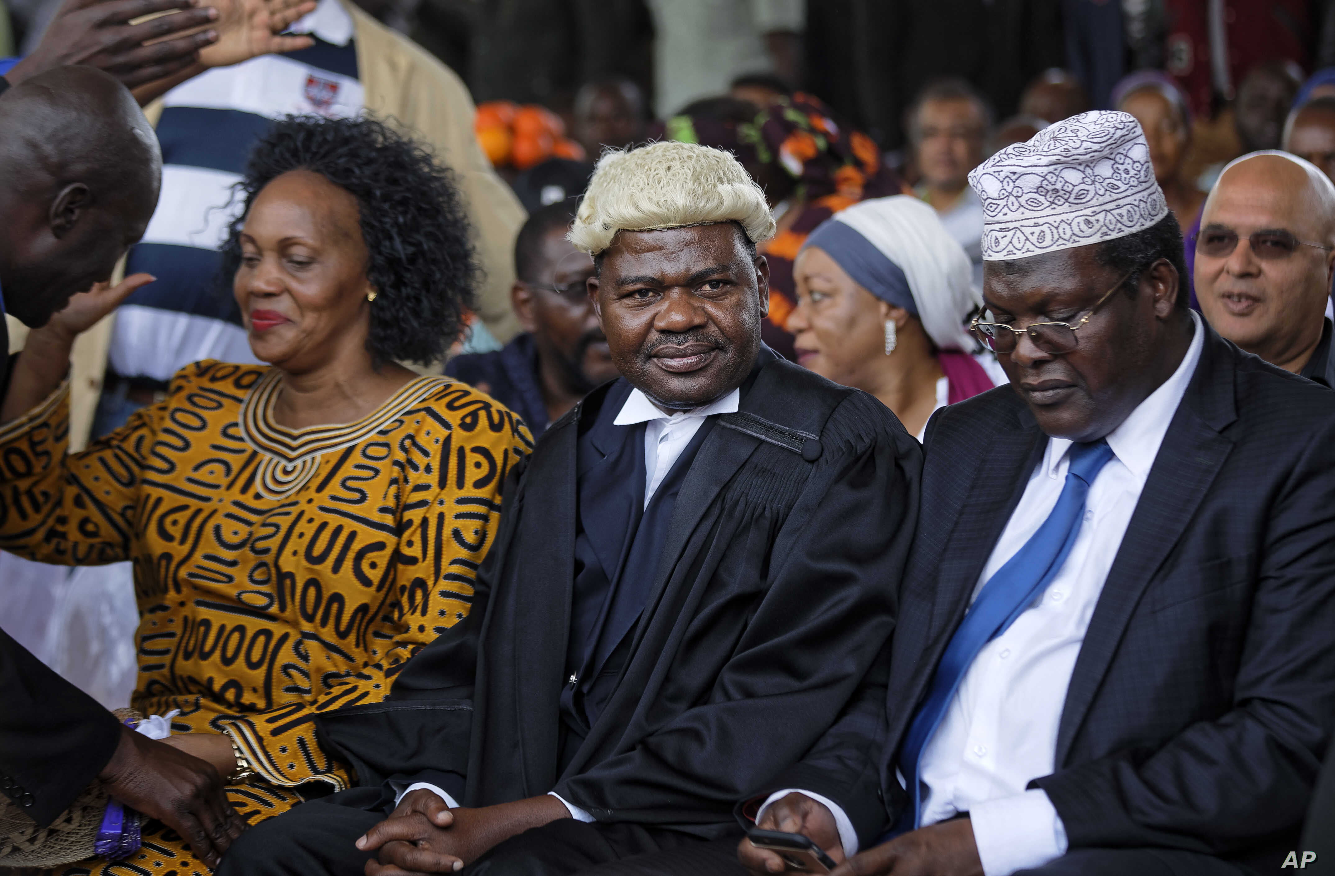 "FILE - Lawyers Miguna Miguna, right, and Tom ""T.J."" Kajwang, center, attend a mock ""swearing-in"" ceremony for opposition leader Raila Odinga at Uhuru Park in downtown Nairobi, Kenya, Jan. 30, 2018."
