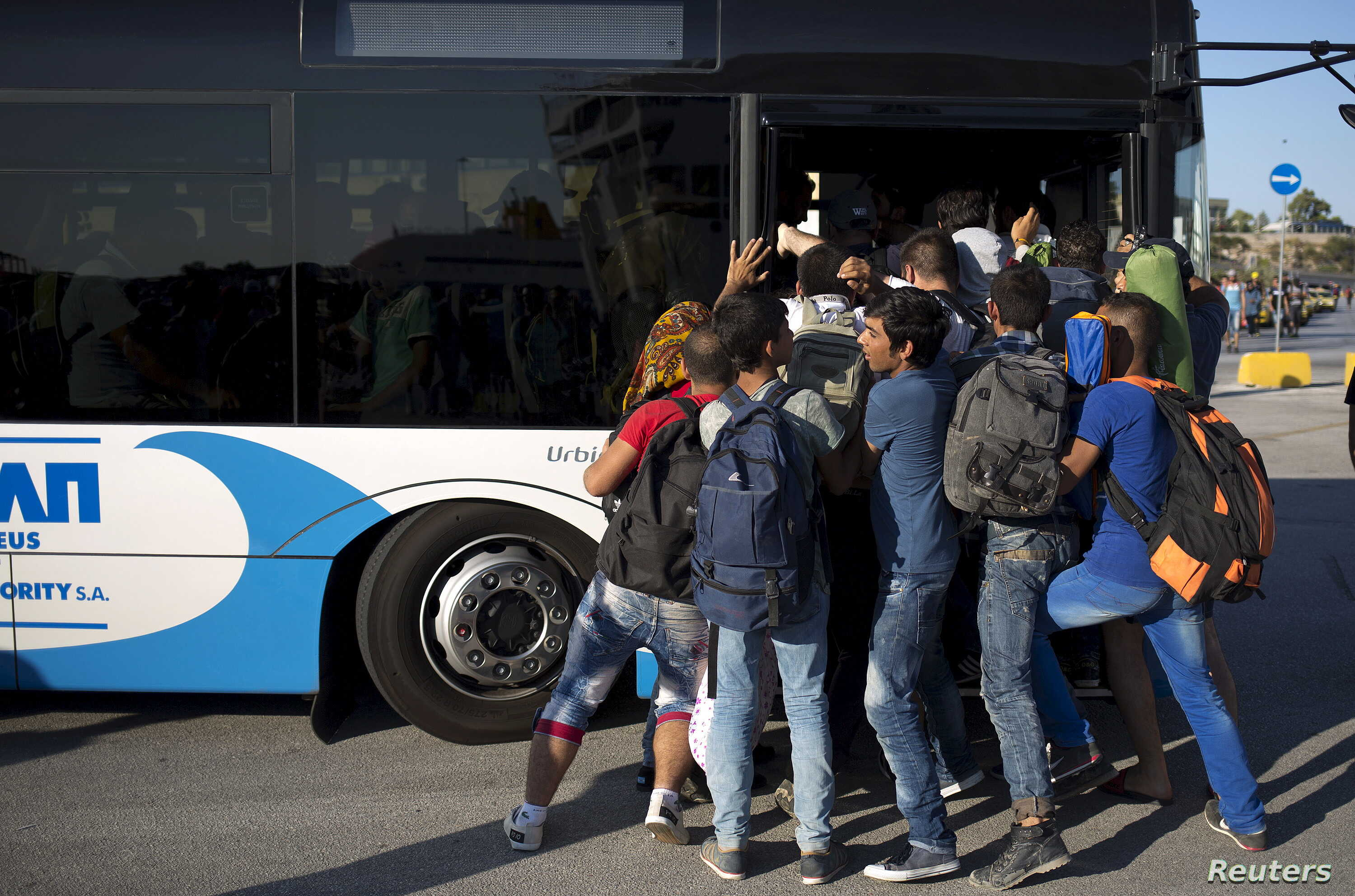 Migrants try to get on a bus following their arrival onboard the Eleftherios Venizelos passenger ship at the port of Piraeus near Athens, Greece, Aug. 29, 2015.
