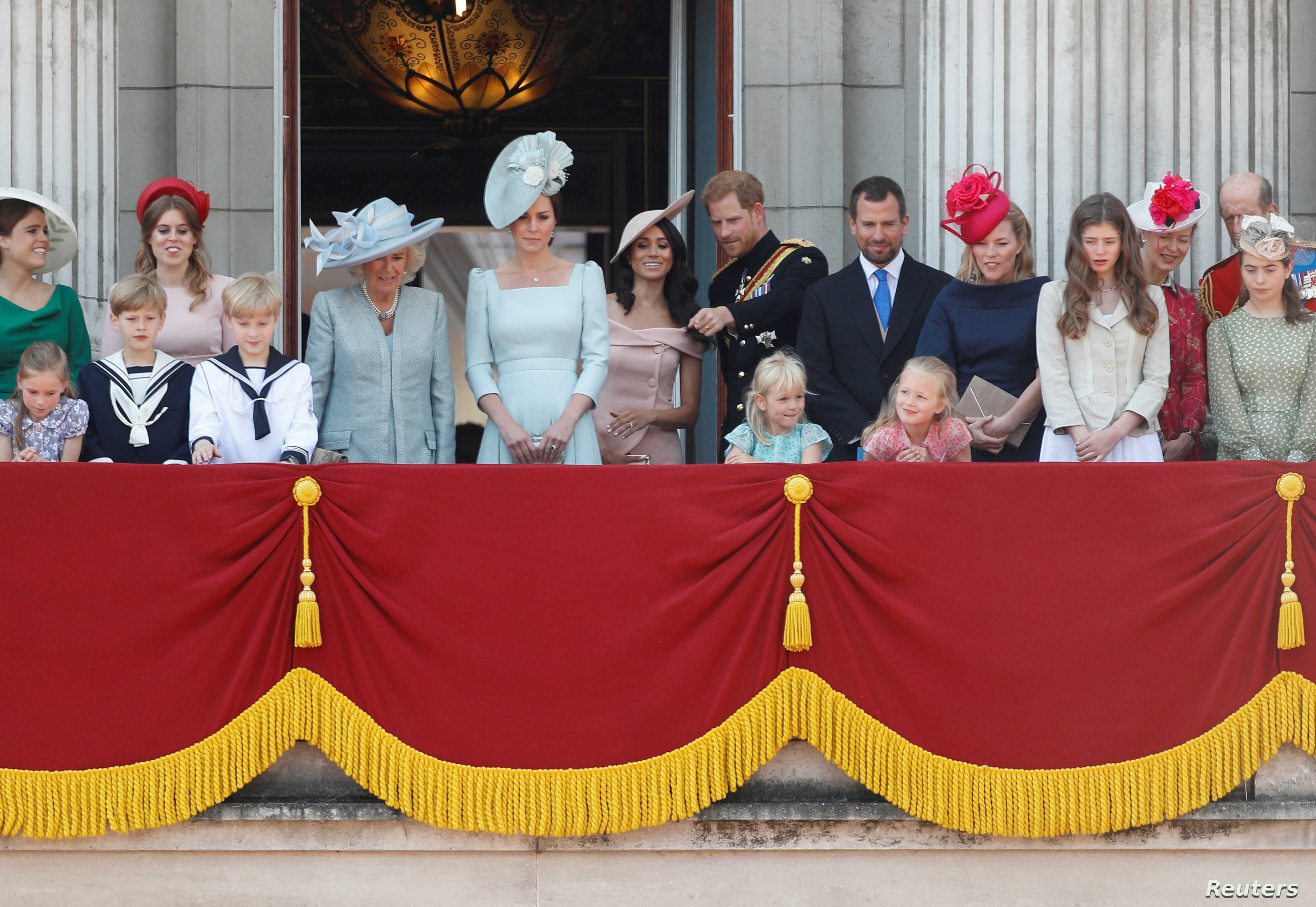 Britain's Prince Harry and Meghan, Duchess of Sussex, along with other members of the British royal family, look down into the palace courtyard from the balcony of Buckingham Palace as part of Trooping the Color parade in central London, Britain, Jun