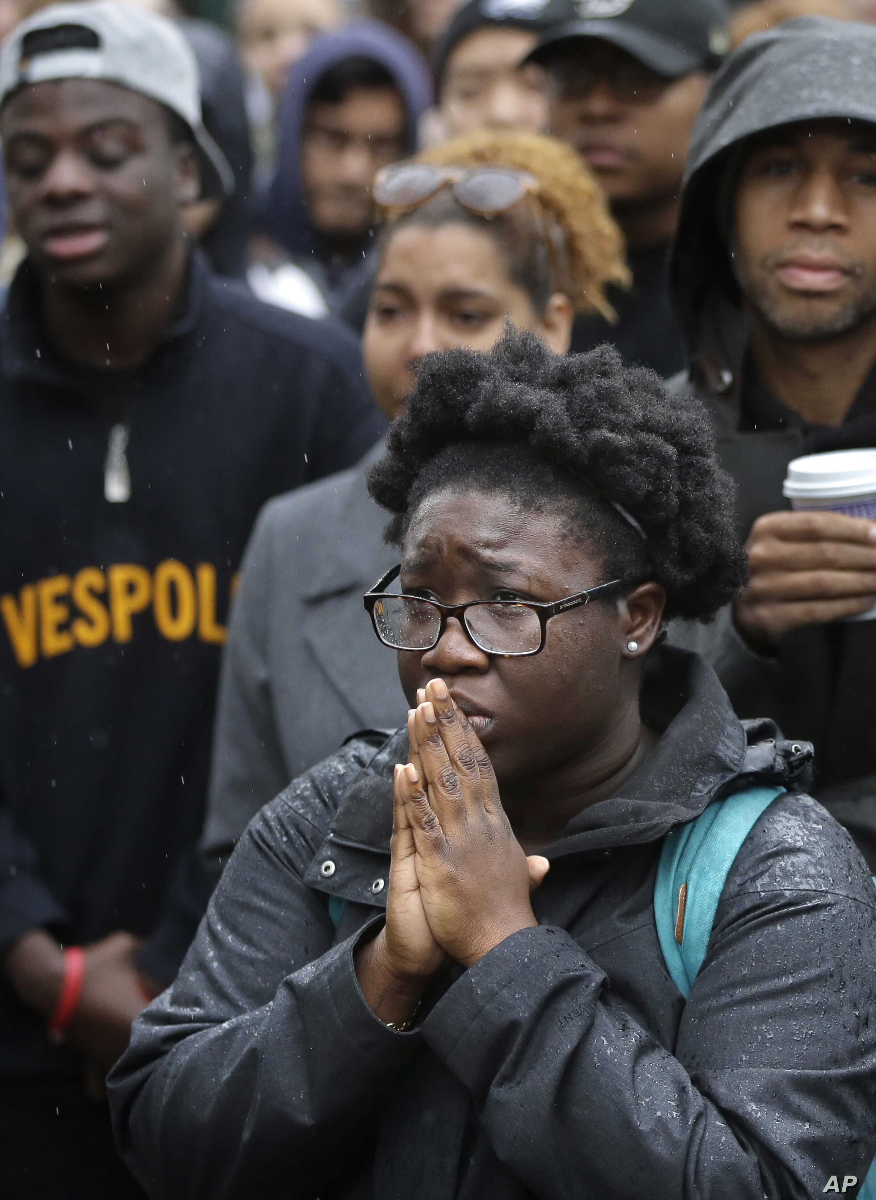 Boston College student Akosua Opokua-Achampong, of Lake Hopatcong, N.J., places her hands together during a solidarity demonstration on the school's campus, in Newton, Mass., Nov. 12, 2015.