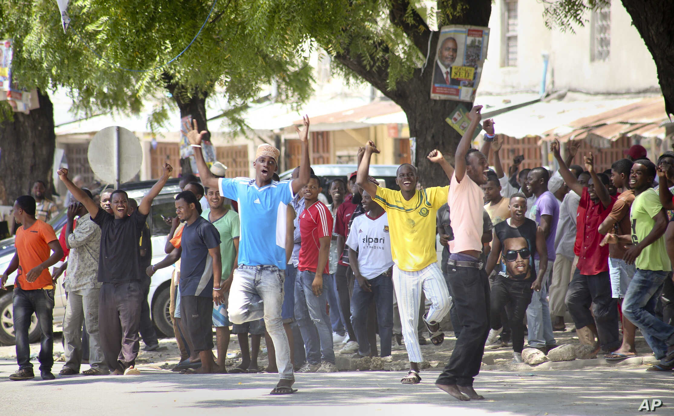 In this photo taken Monday, Oct. 26th, 2015 and made available Wednesday, Oct. 28th, 2015, youths supporting the opposition party dance and chant, predicting a win for their candidate, outside the Electoral Commission office in Stone Town, Zanzibar, ...