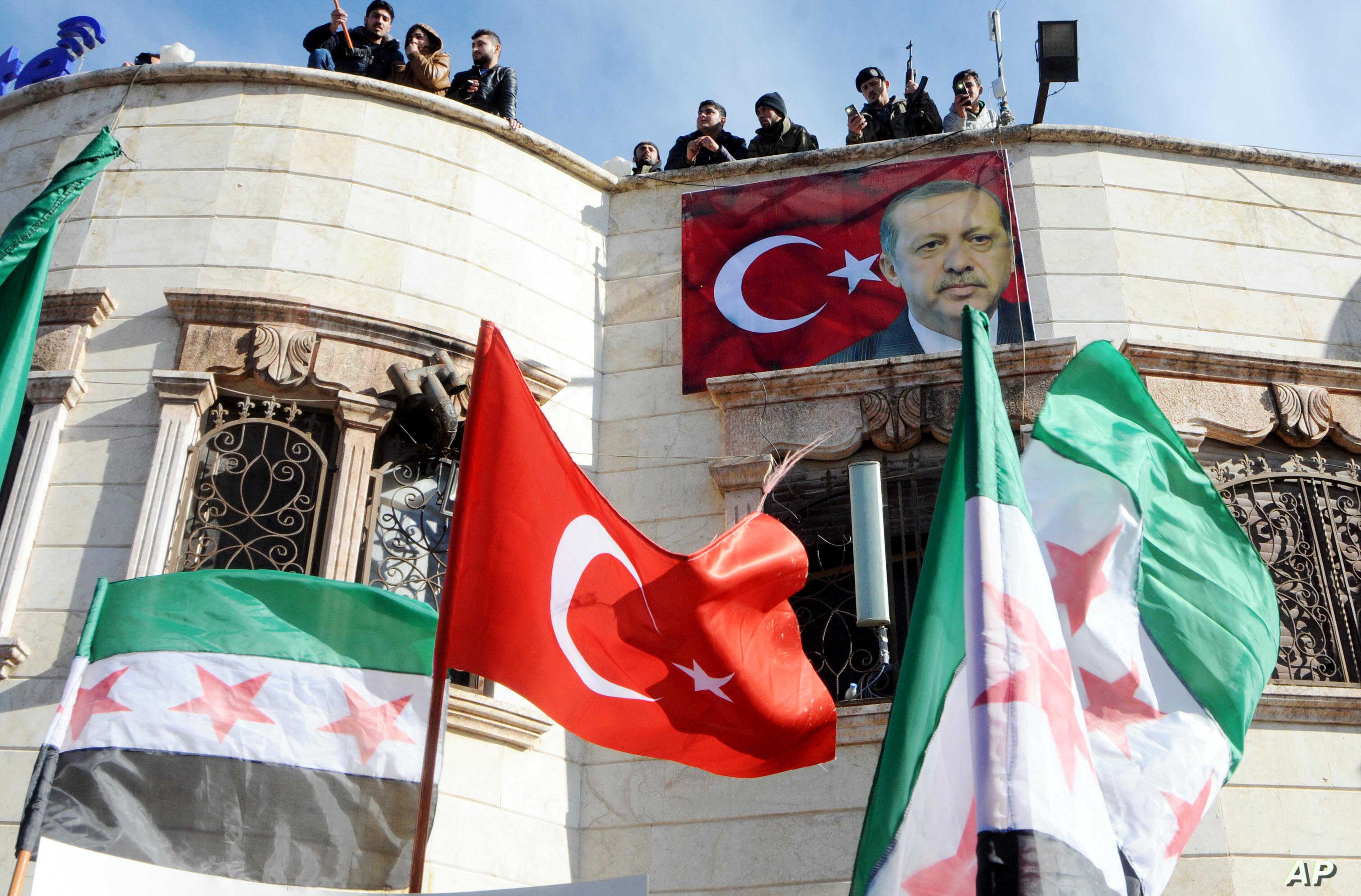 Turkey-backed Free Syrian Army, FSA, fighters stand on the roof of a building with a poster of Turkey's President Recep Tayyip Erdogan hanging on it in the Syrian town of Azez near the border with Turkey, Jan. 19, 2018.