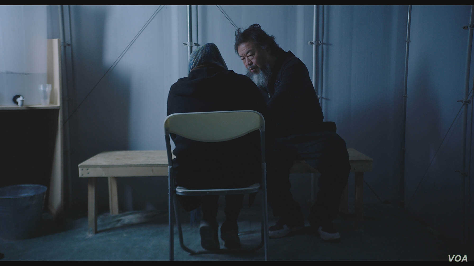 Ai Weiwei talks to refugee in scene from 'Human Flow' documentary.
