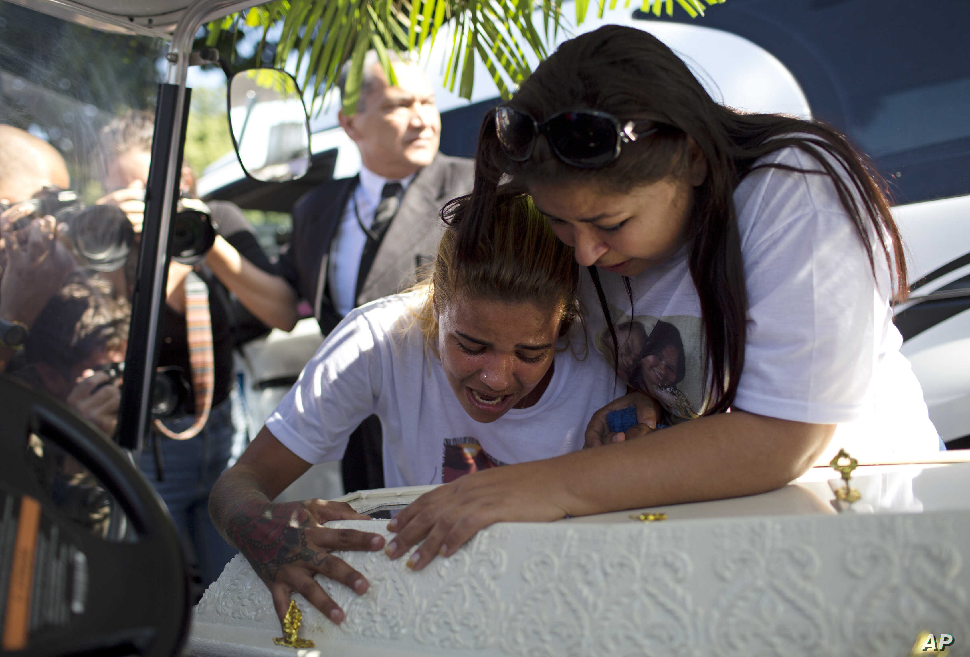 FILE - Adriana Maria dos Santos, mother of the late Vanessa do Santos, and a friend, Laisa, cry over Vanessa's casket during her burial in Rio de Janeiro, Brazil, July 6, 2017. The 10-year-old child was killed two days earlier after being hit in the ...