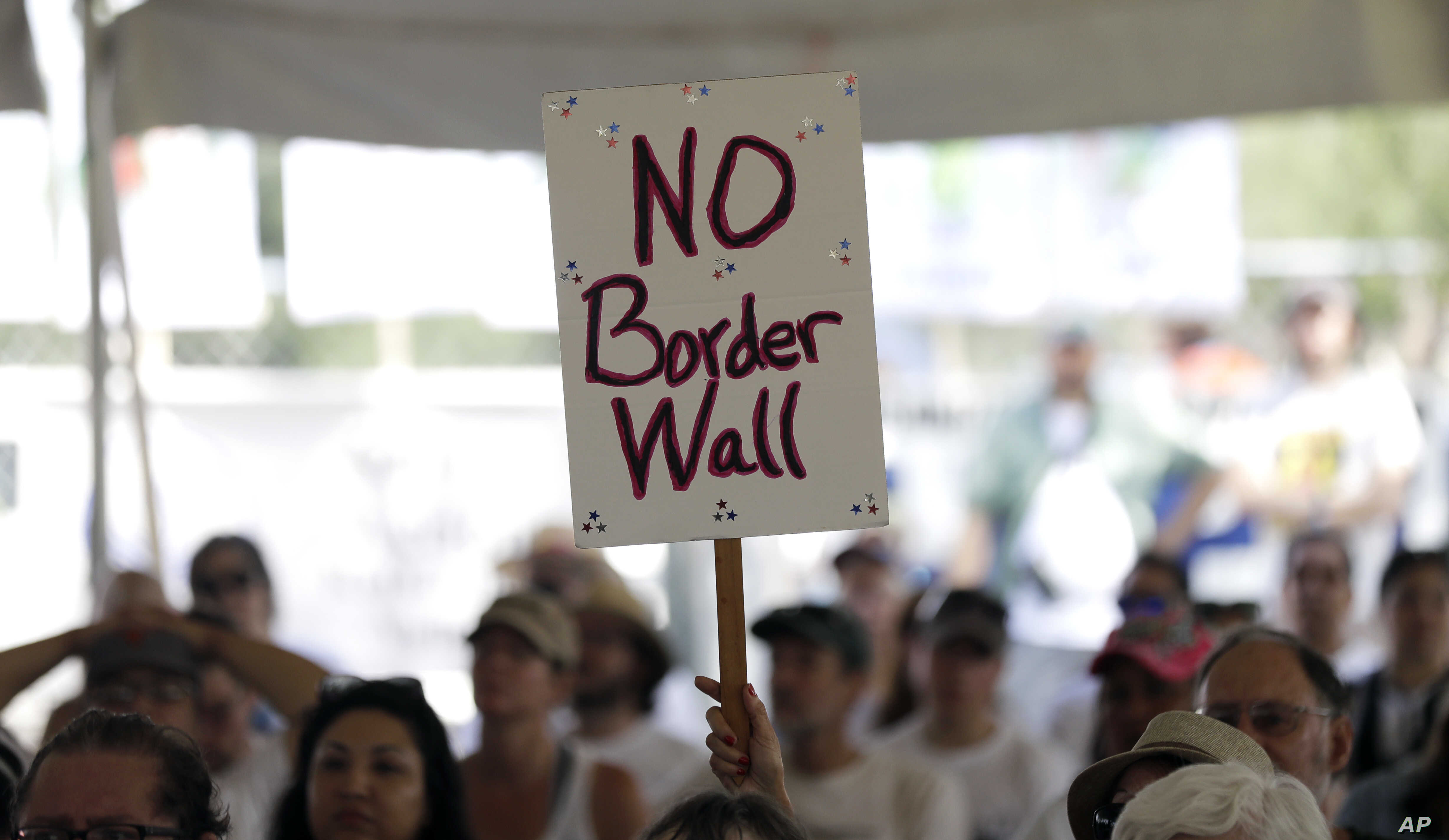 """FILE - A """"no border wall"""" sign is held during a rally to oppose the wall the U.S. government wants to build on the river separating Texas and Mexico, Aug. 12, 2017, in Mission, Texas."""