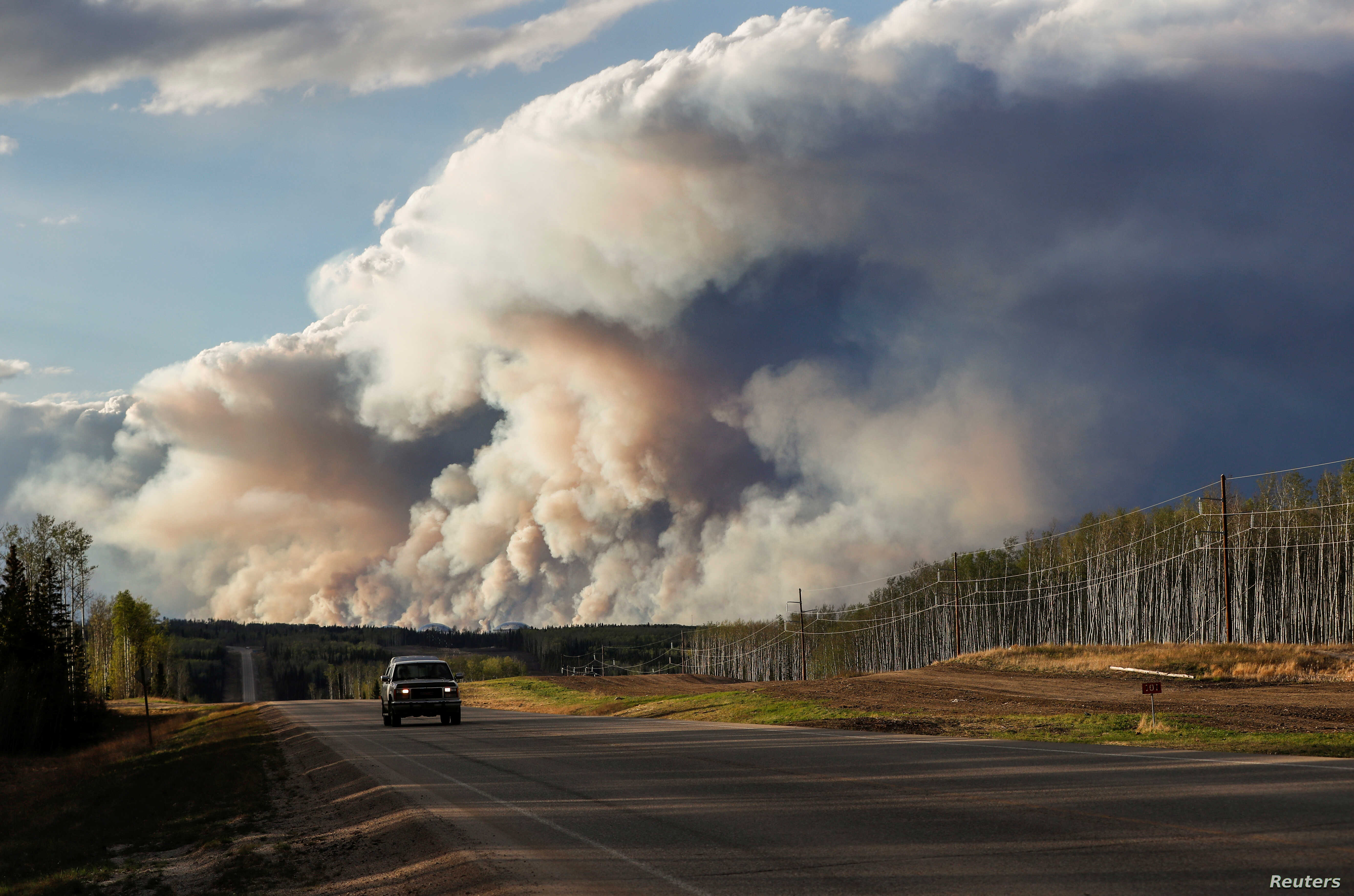 Smoke billows from the Fort McMurray wildfires as a truck drives down the highway in Kinosis, Alberta, Canada, May 5, 2016.