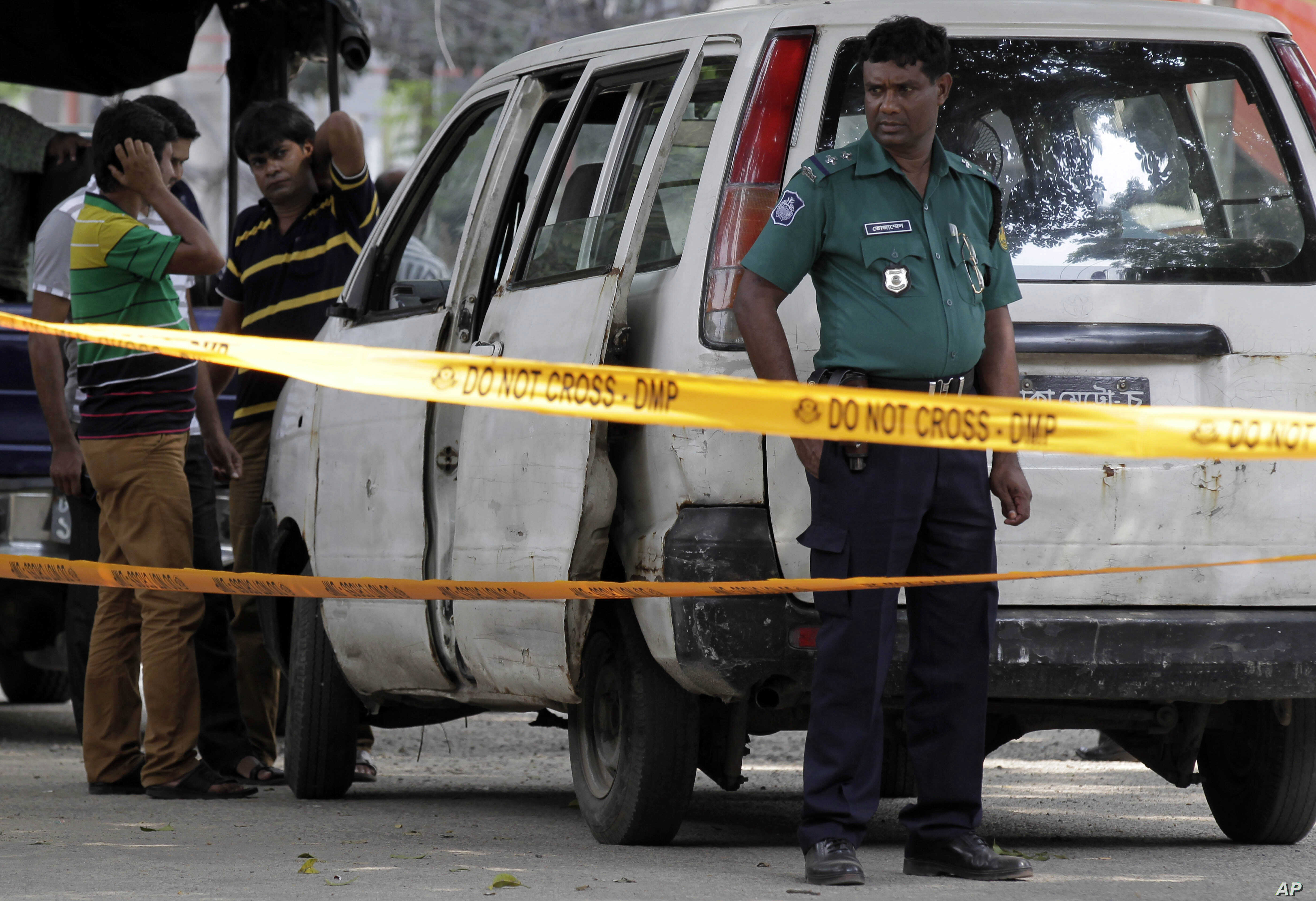 Members of Bangladeshi police and detective branch stand by the site where Italian citizen Cesare Tavella was gunned down by unidentified assailants in Dhaka, Bangladesh, Sept. 29, 2015.