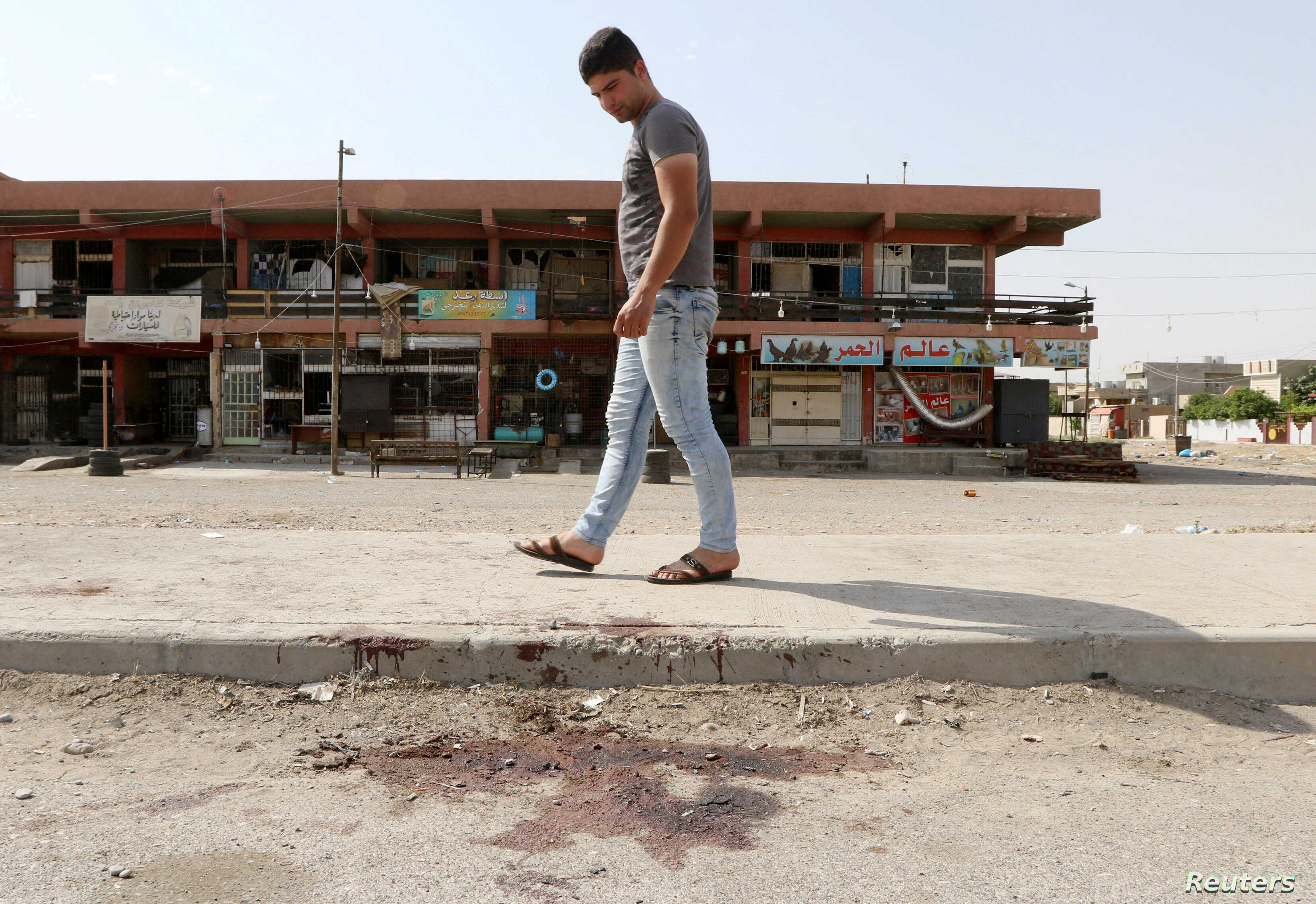 A man looks at bloodstains on a roadway after a bomb explosion in the ethnically-mixed Iraqi oil city of Kirkuk, Iraq, June 9, 2018.