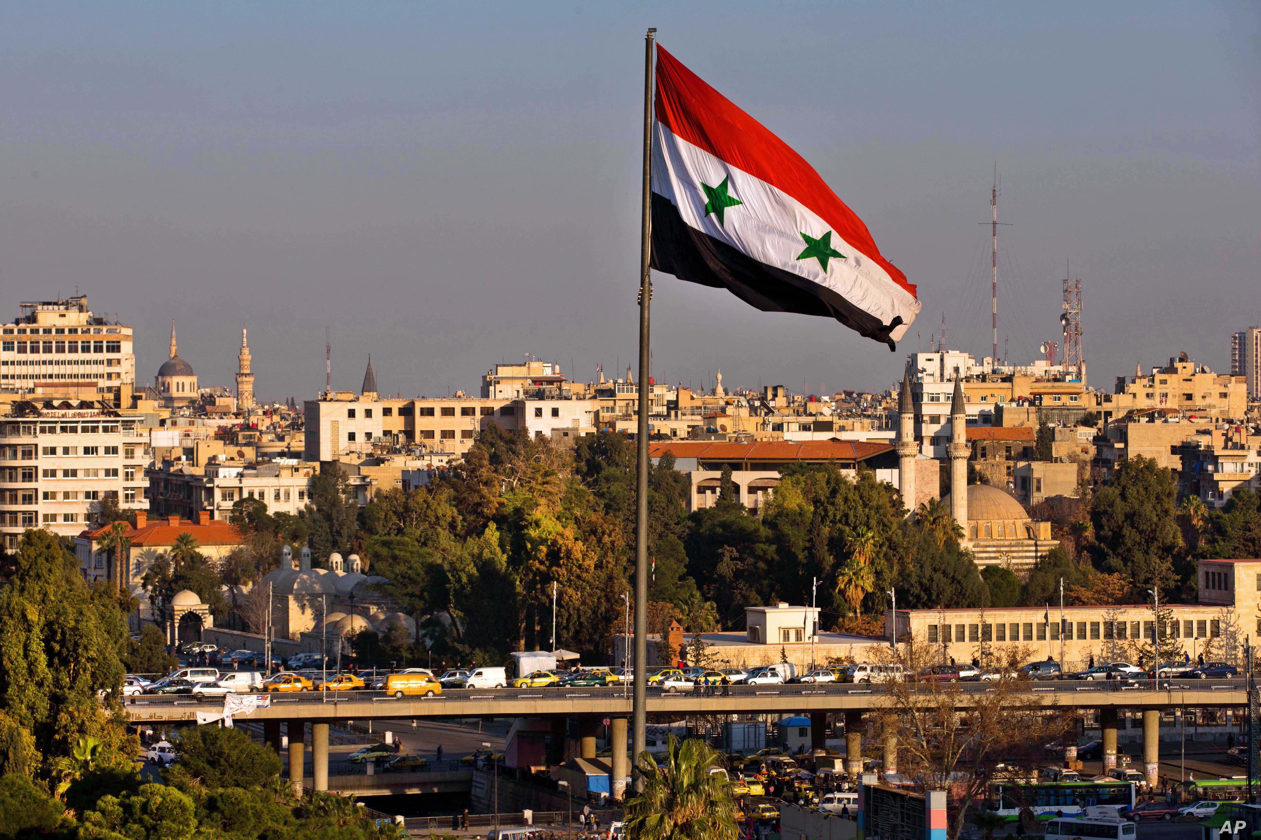 A Syrian national flag waves as vehicles move slowly on a bridge during rush hour, in Damascus, Syria, Feb. 28, 2016.