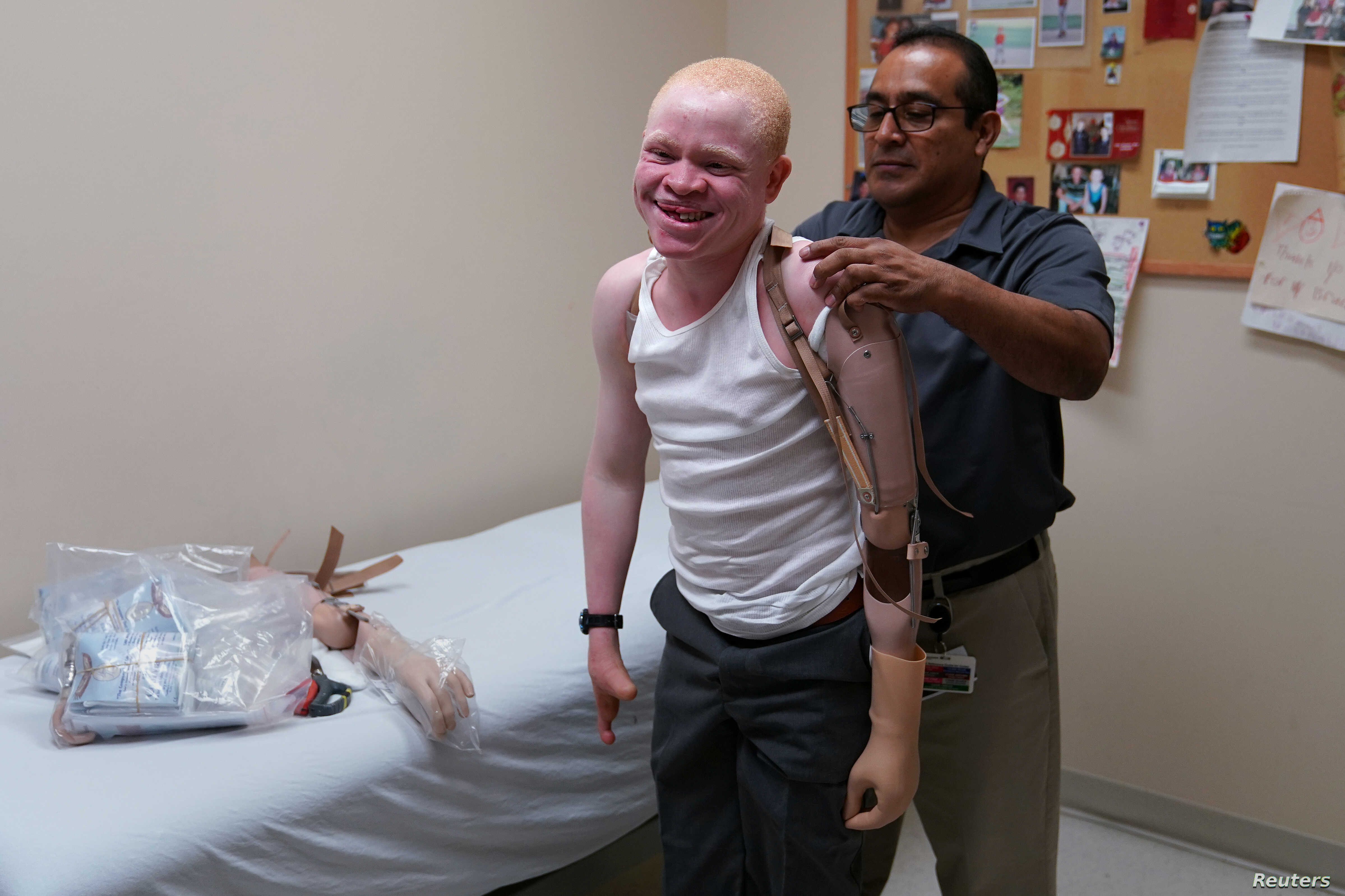 A worker helps Emmanuel Rutema, a Tanzanian with albinism who had his arm chopped off in a superstition-driven attack, put on a new prosthetic arm at the Shriners Hospital in Philadelphia, Pennsylvania, May 30, 2017.