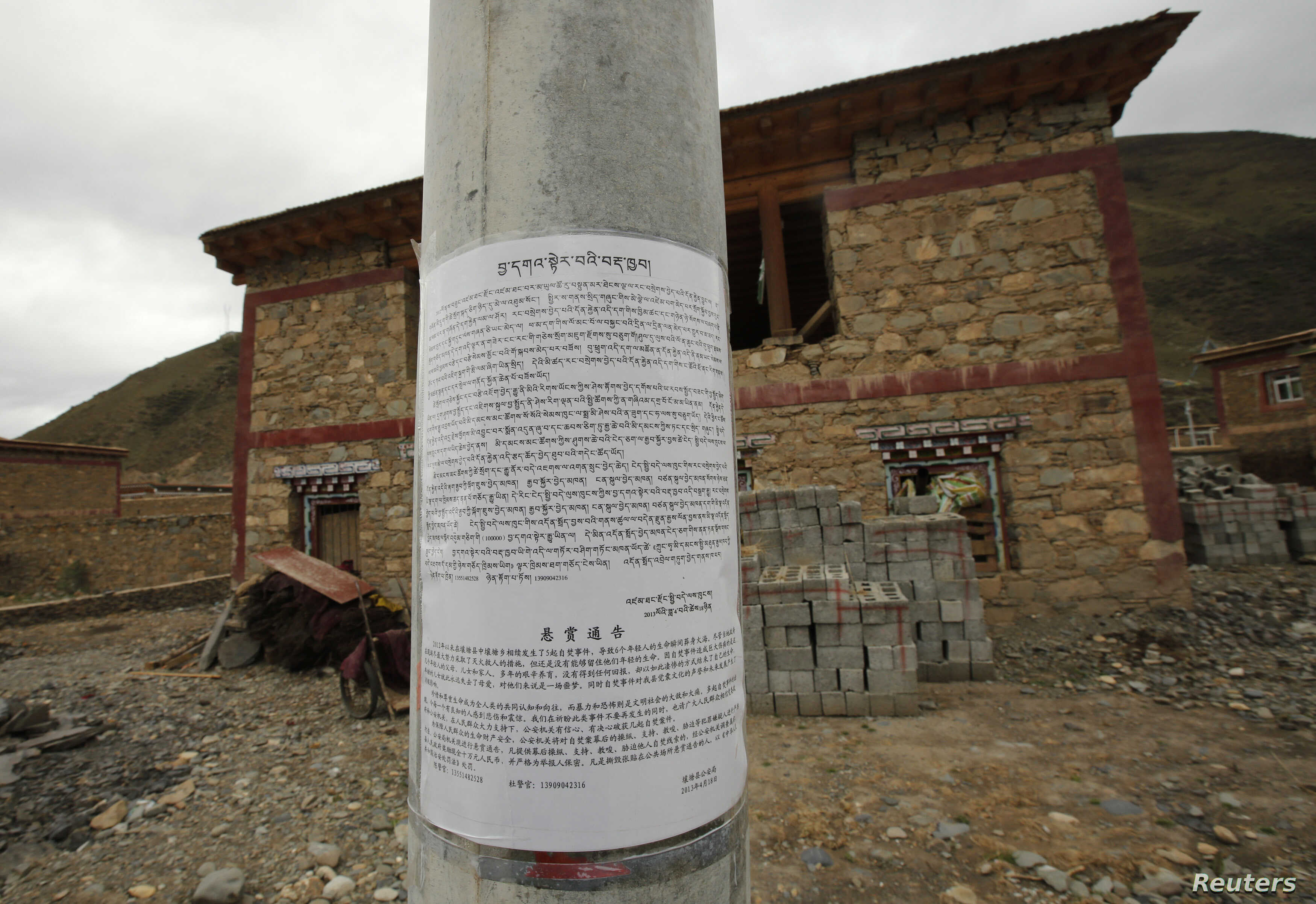 "FILE - A notice about self-immolations, which offers a reward of 100,000 yuan ($16,319) for information on those ""masterminding, supporting, abetting and coercing others to self-immolate,"" is posted in Barma township, May 16, 2013."