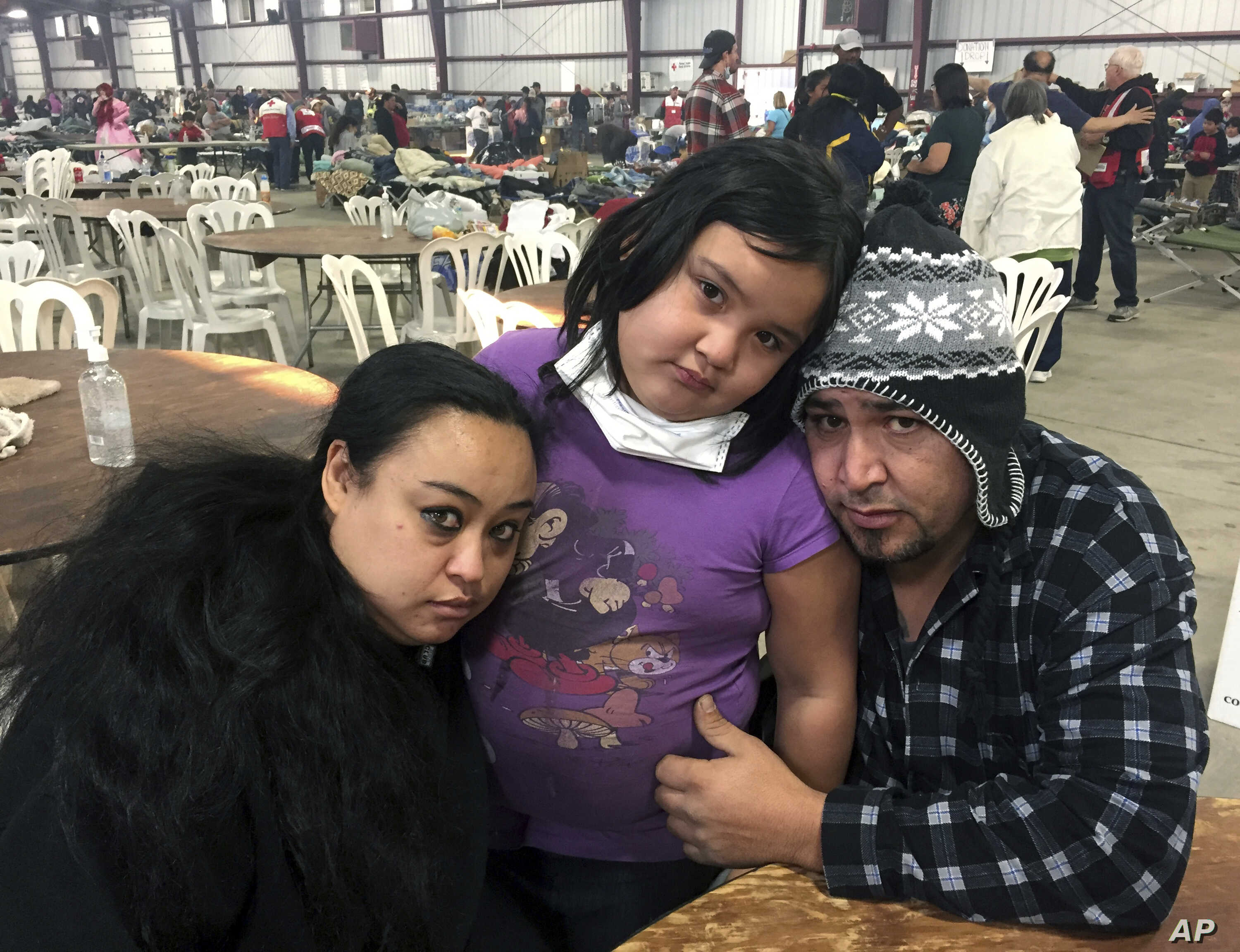 Wildfire survivors, Marolyn Romero-Sim, left, with Hugo Romero-Rodriguez, middle, and their 9-year-old daughter, Milagros, sit inside the evacuation center at the Ventura County Fairgrounds in Ventura, Calif. Their RV burned up with all their possess...