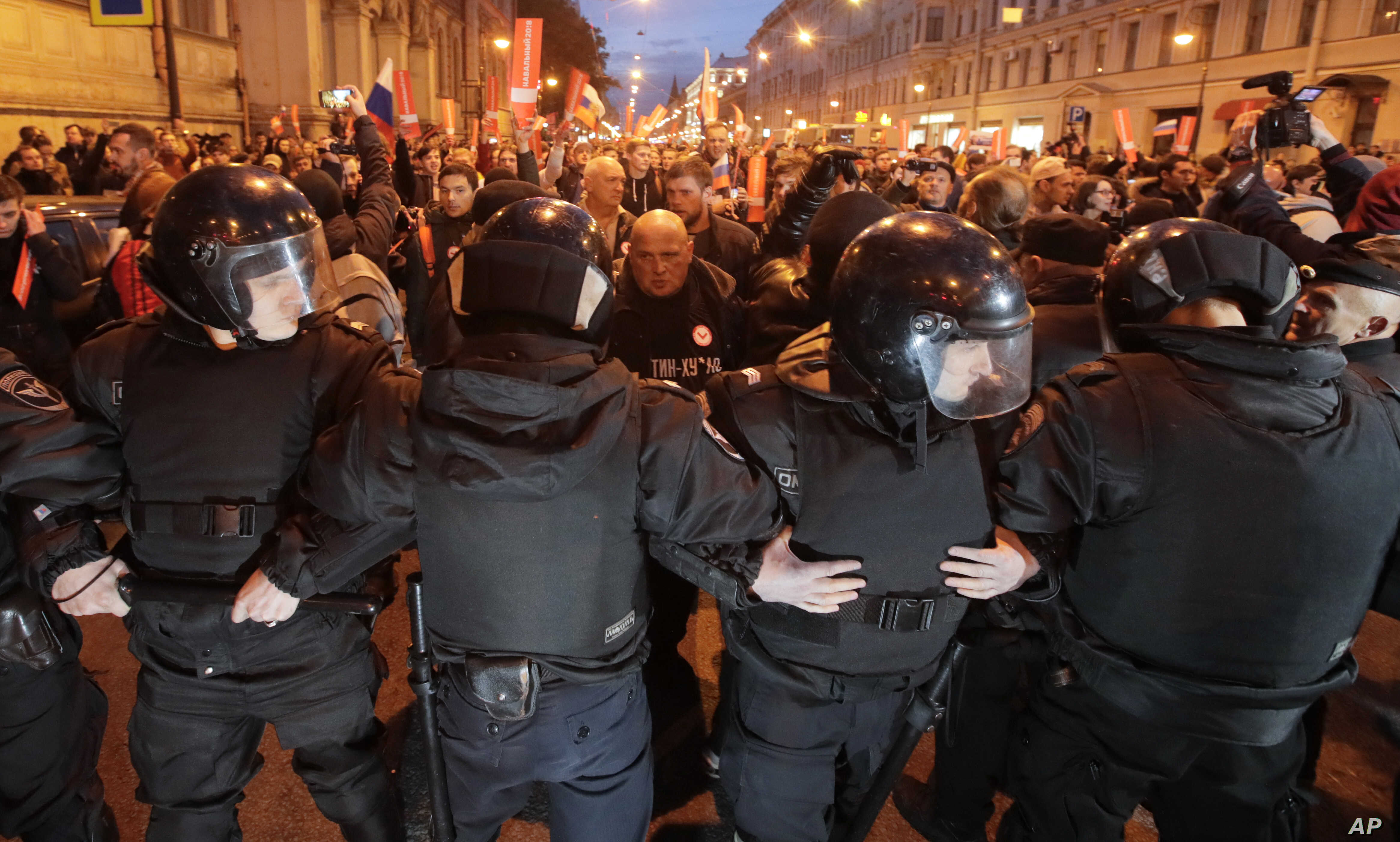 Riot police officers block the way to protesters during a rally in St. Petersburg, Russia, Oct. 7, 2017.