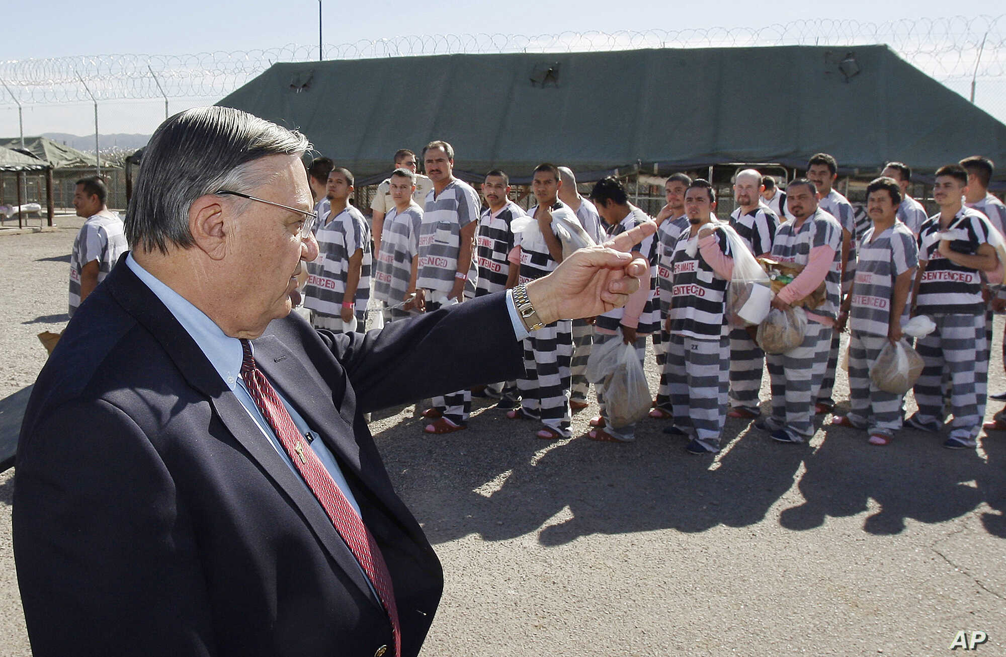 FILE - In this Feb. 4, 2009, file photo, Maricopa County Sheriff Joe Arpaio, left, orders approximately 200 convicted illegal immigrants handcuffed together and moved into a separate area of Tent City, for incarceration until their sentences are serv...