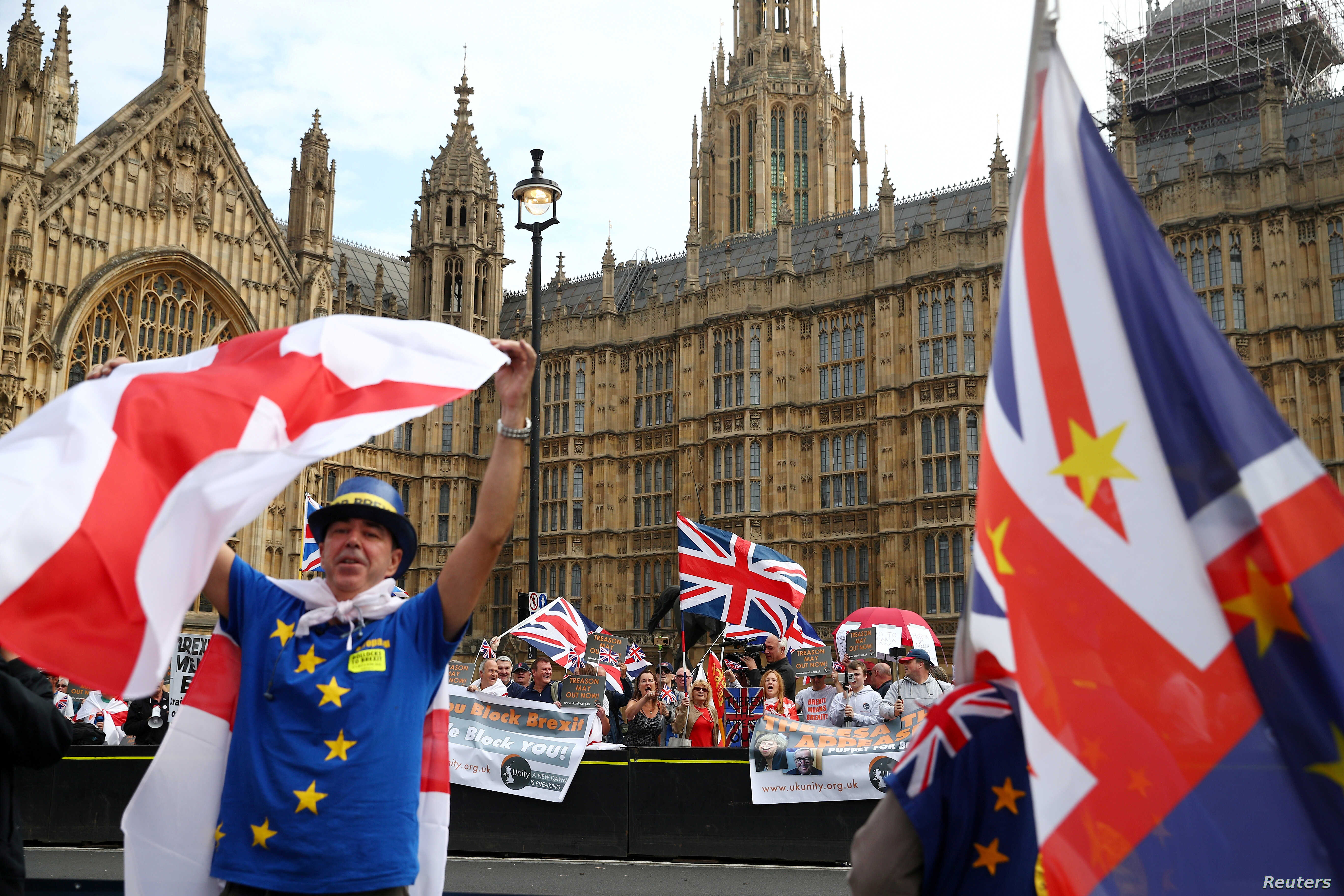FILE - Pro- and anti-Brexit protesters demonstrate on opposite sides of the road outside the Houses of Parliament in London, September 5, 2018.