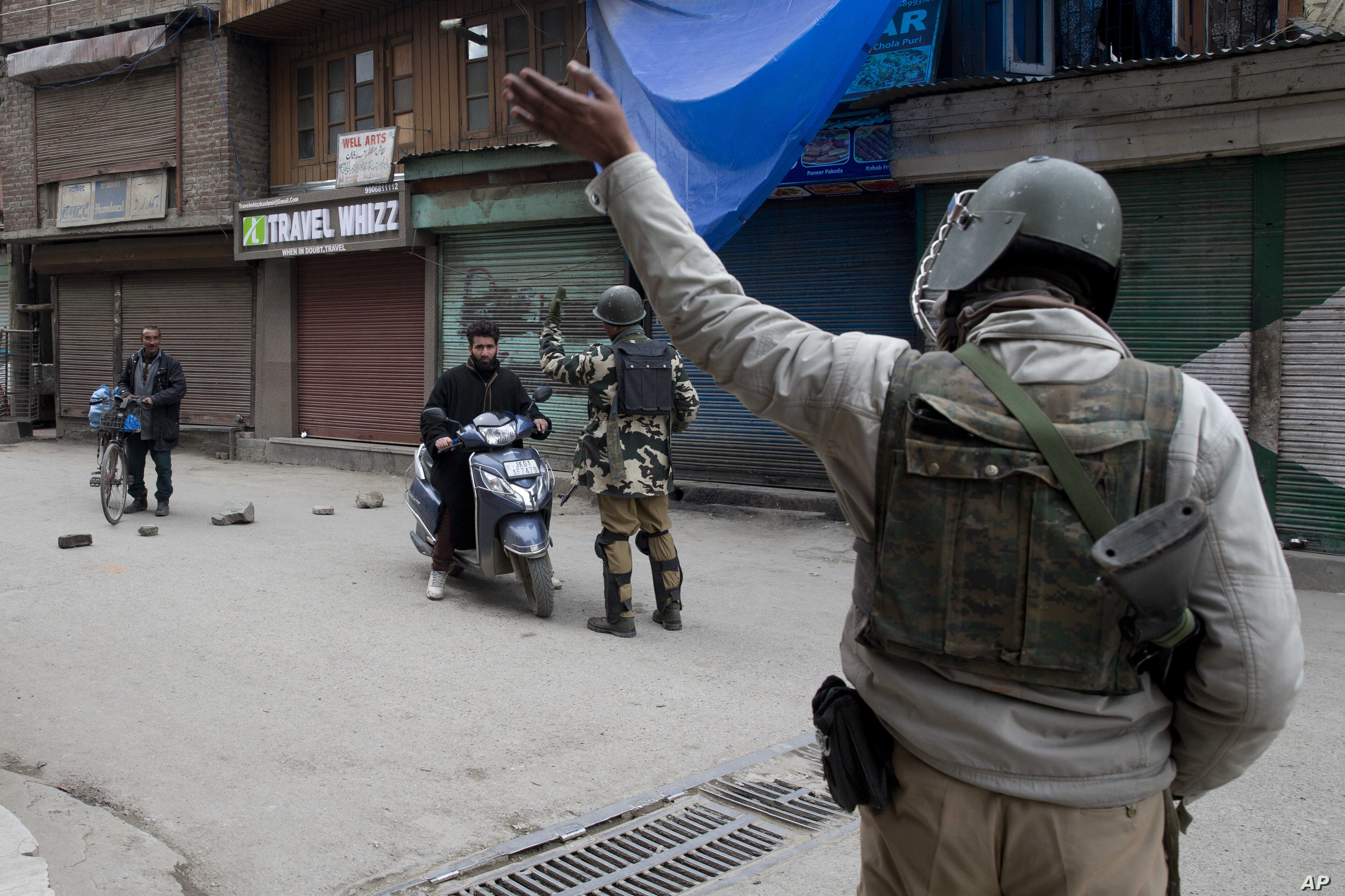 Indian paramilitary soldiers order commuters to turn back during a security lockdown in downtown Srinagar, Indian-controlled Kashmir, March 1, 2019.
