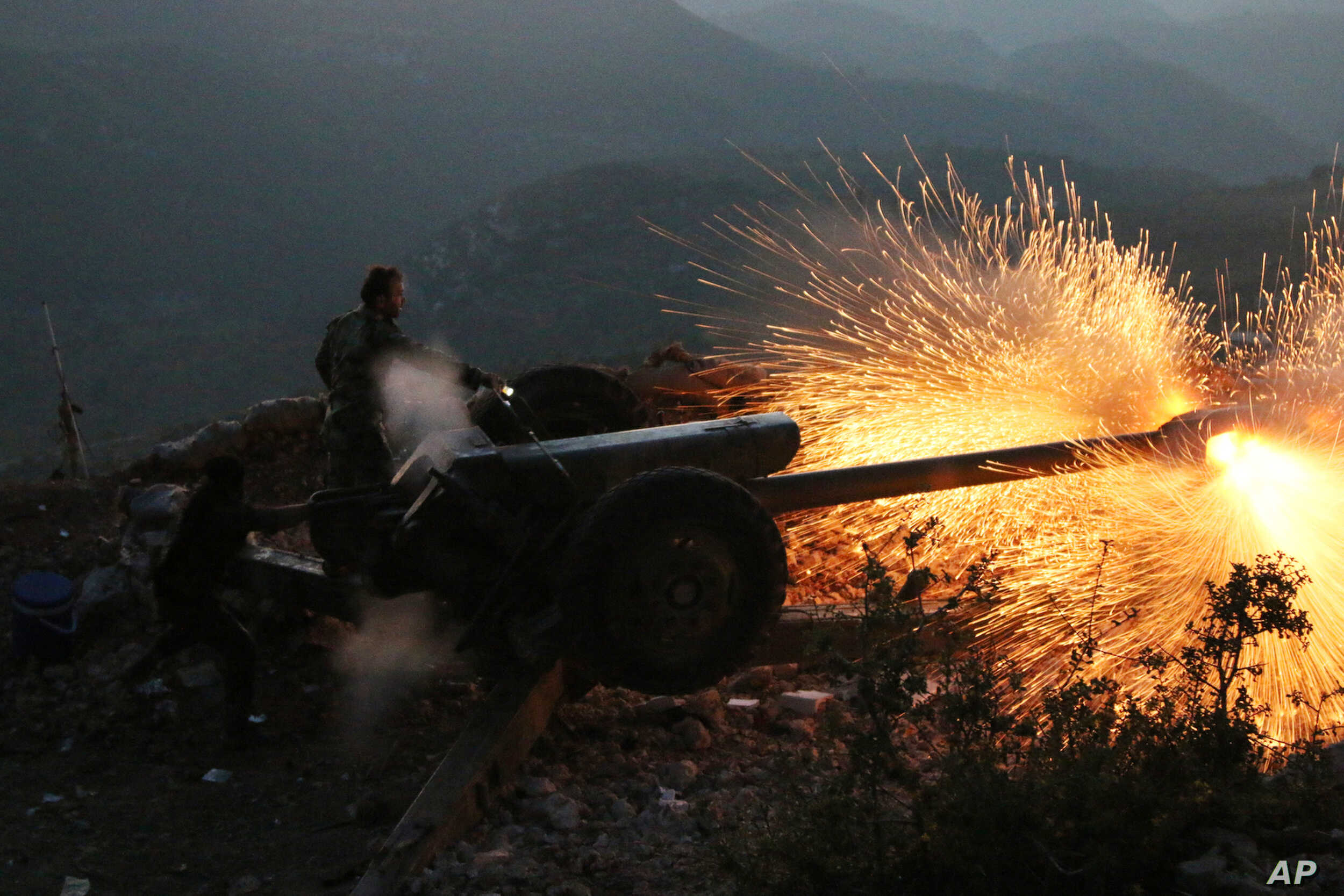 Syrian army personnel backed by Russian airstrikes fire cannon in Latakia province, near the border with Turkey, Oct. 10, 2015.