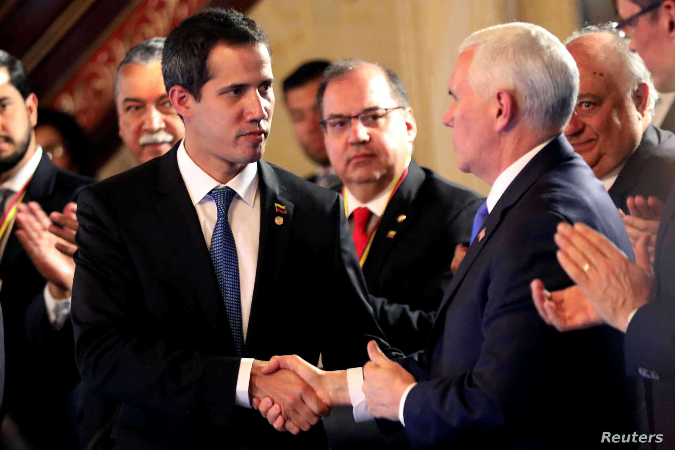 U.S. Vice President Mike Pence and Venezuelan opposition leader Juan Guaido, who many nations have recognized as the country's rightful interim ruler, shake hands during a meeting of the Lima Group in Bogota, Colombia, Feb. 25, 2019.