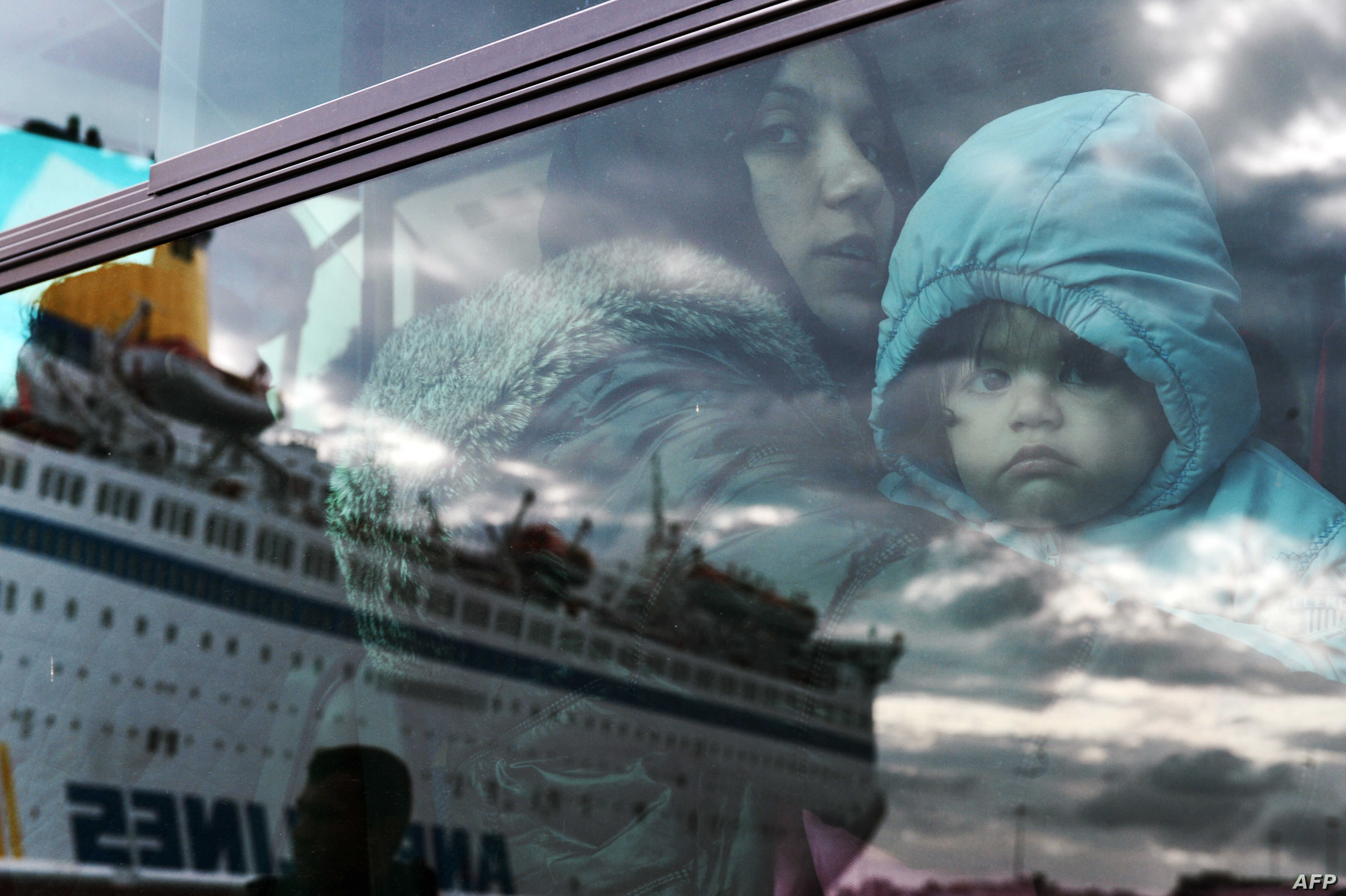 A woman and a child peer from a bus, after migrants and refugees disembarked  from a government chartered ferry, seen in reflection, in the port of Piraeus in Athens on Nov. 27, 2015.