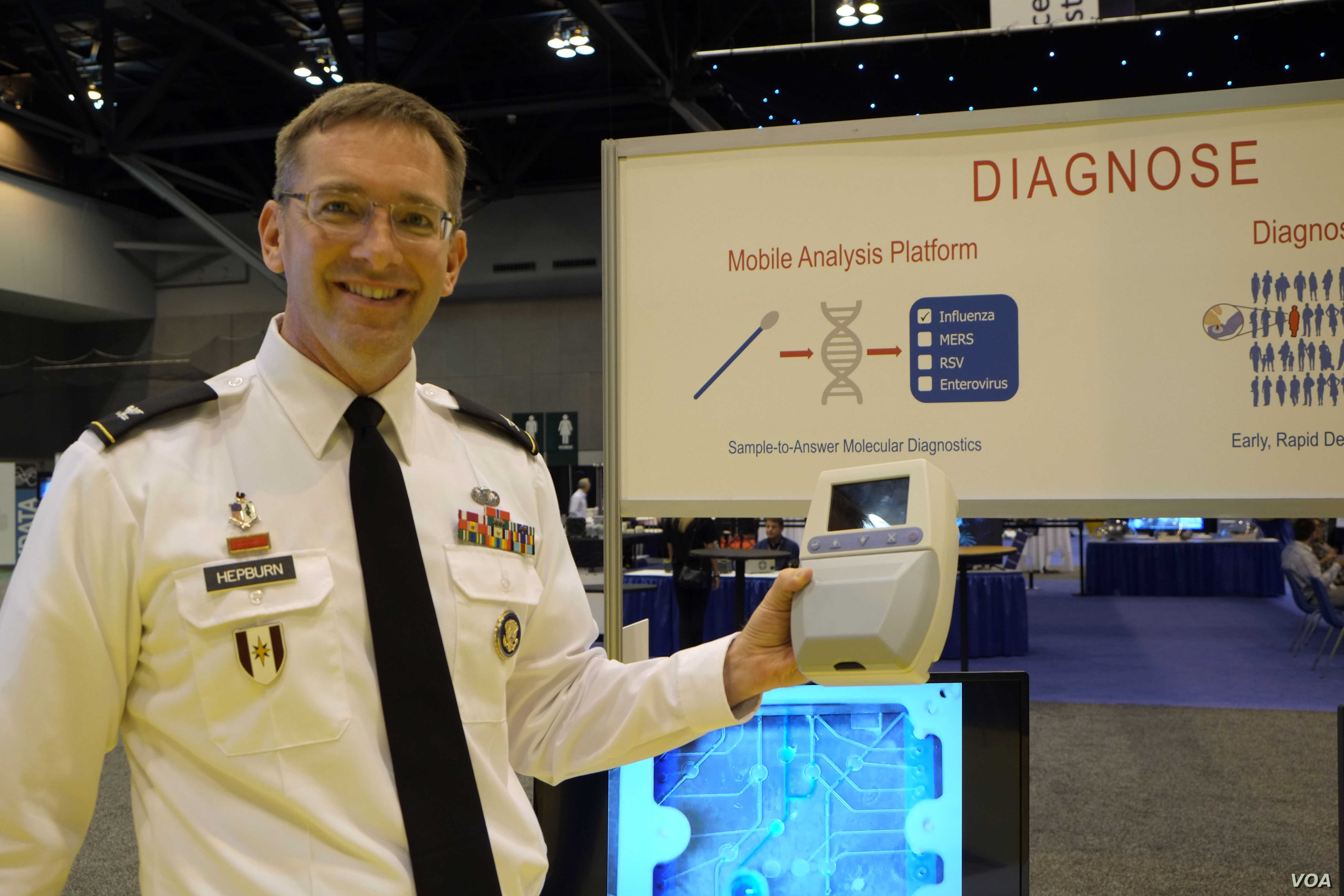 Dr. Matt Hepburn displays a portable diagnostic device for rapid testing of infectious diseases. Trained laboratory workers aren't needed, and treatment can begin immediately, instead of waiting for results from a faraway lab. (Credit: Art Chimes/V...