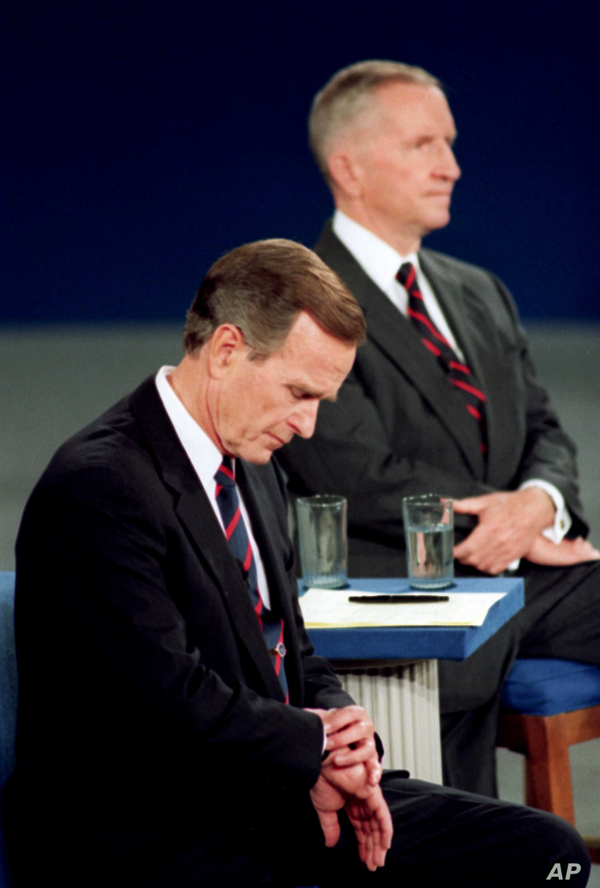FILE - President George H.W. Bush checks his watch during the 1992 presidential campaign debate with Independent Ross Perot and Democrat Bill Clinton, not shown. Presidential candidates and their running mates often find that campaign debates turn o...