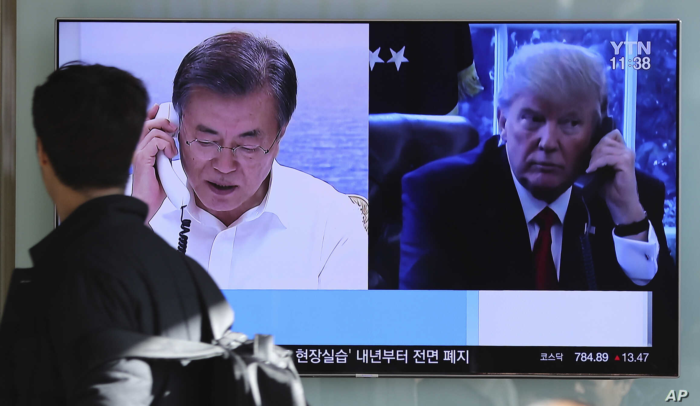 A man walks by a TV screen showing a local news program reporting about North Korea's missile launch with an images of U.S. President Donald Trump and South Korean President Moon Jae-in at the Seoul Railway Station in Seoul, South Korea, Friday, Dec....