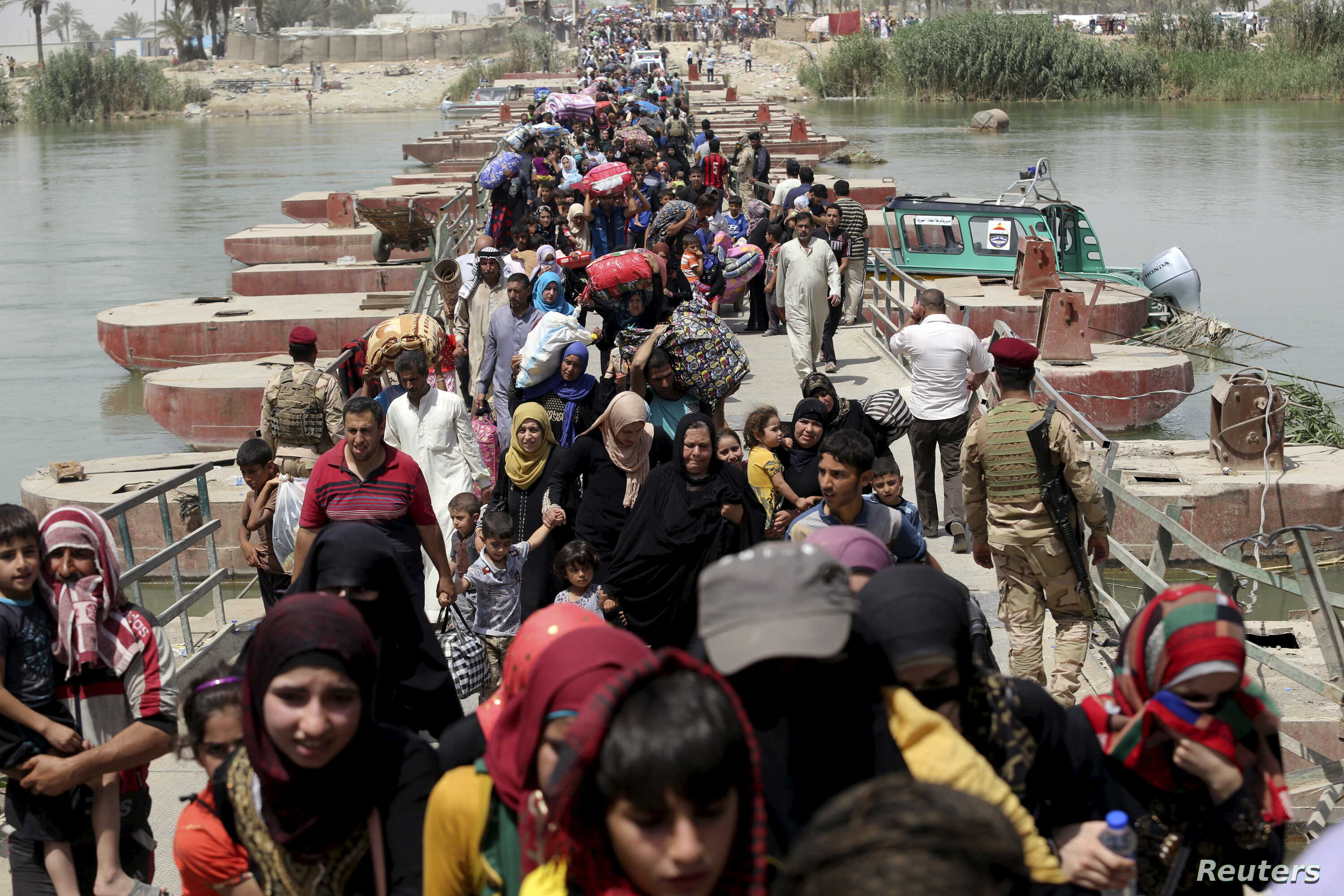Displaced Sunni people fleeing Ramadi cross a bridge outside Baghdad, May 24, 2015. Iraqi forces recaptured territory from advancing Islamic State militants near the recently fallen city of Ramadi on Sunday.