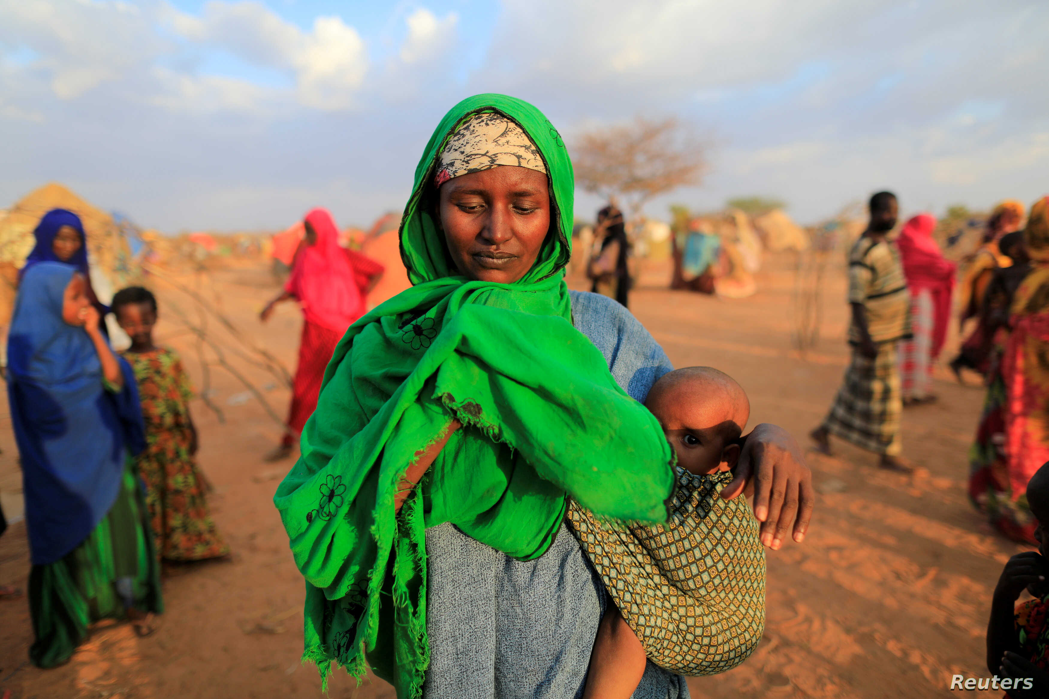 FILE - An internally displaced woman from a drought-hit area reacts after she complains about the lack of food at makeshift settlement area in Dollow, Somalia.