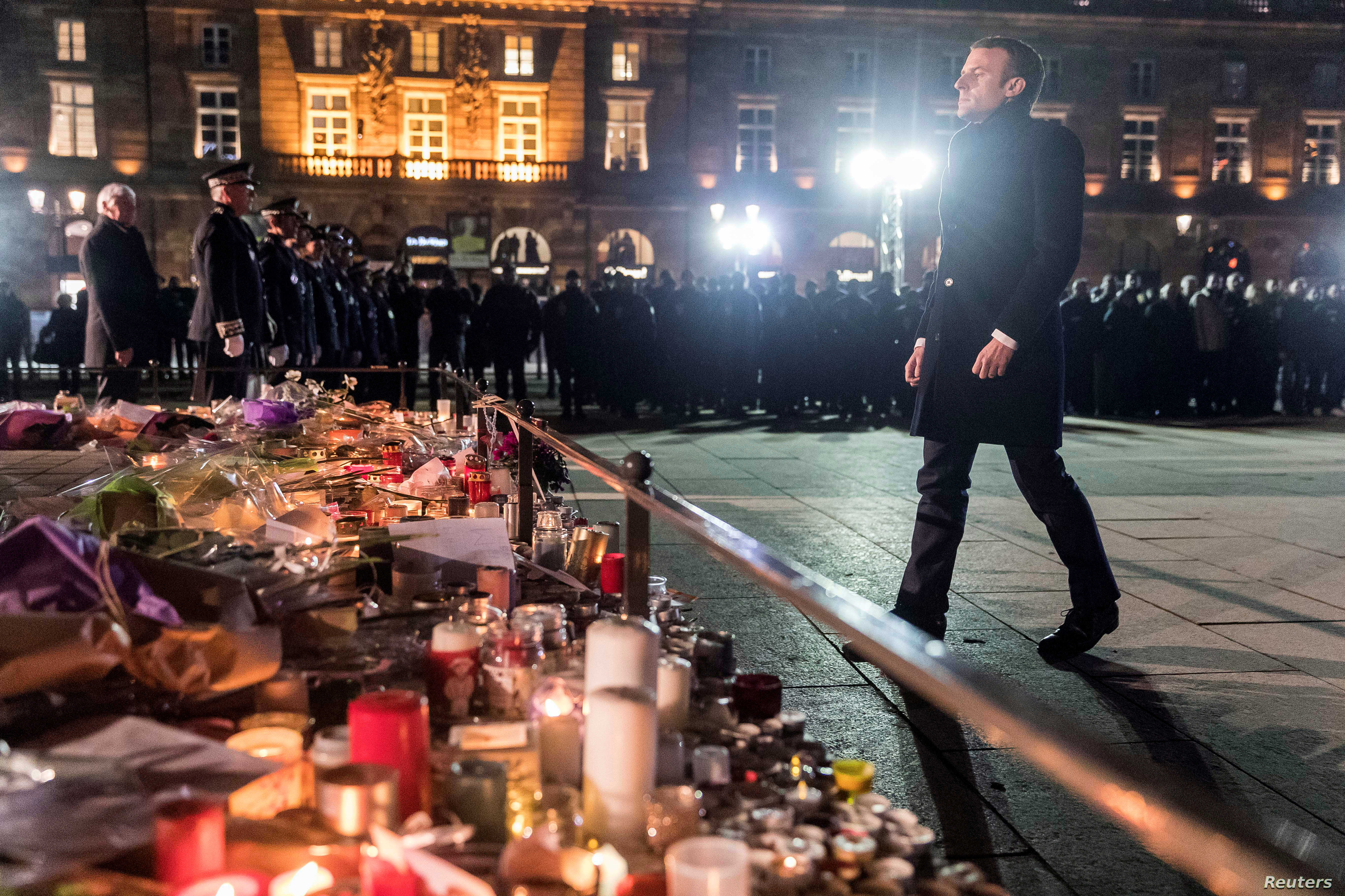French President Emmanuel Macron pays homage to the victims of the attack, at a monument near the Christmas market in Strasbourg, France, Dec. 14, 2018.