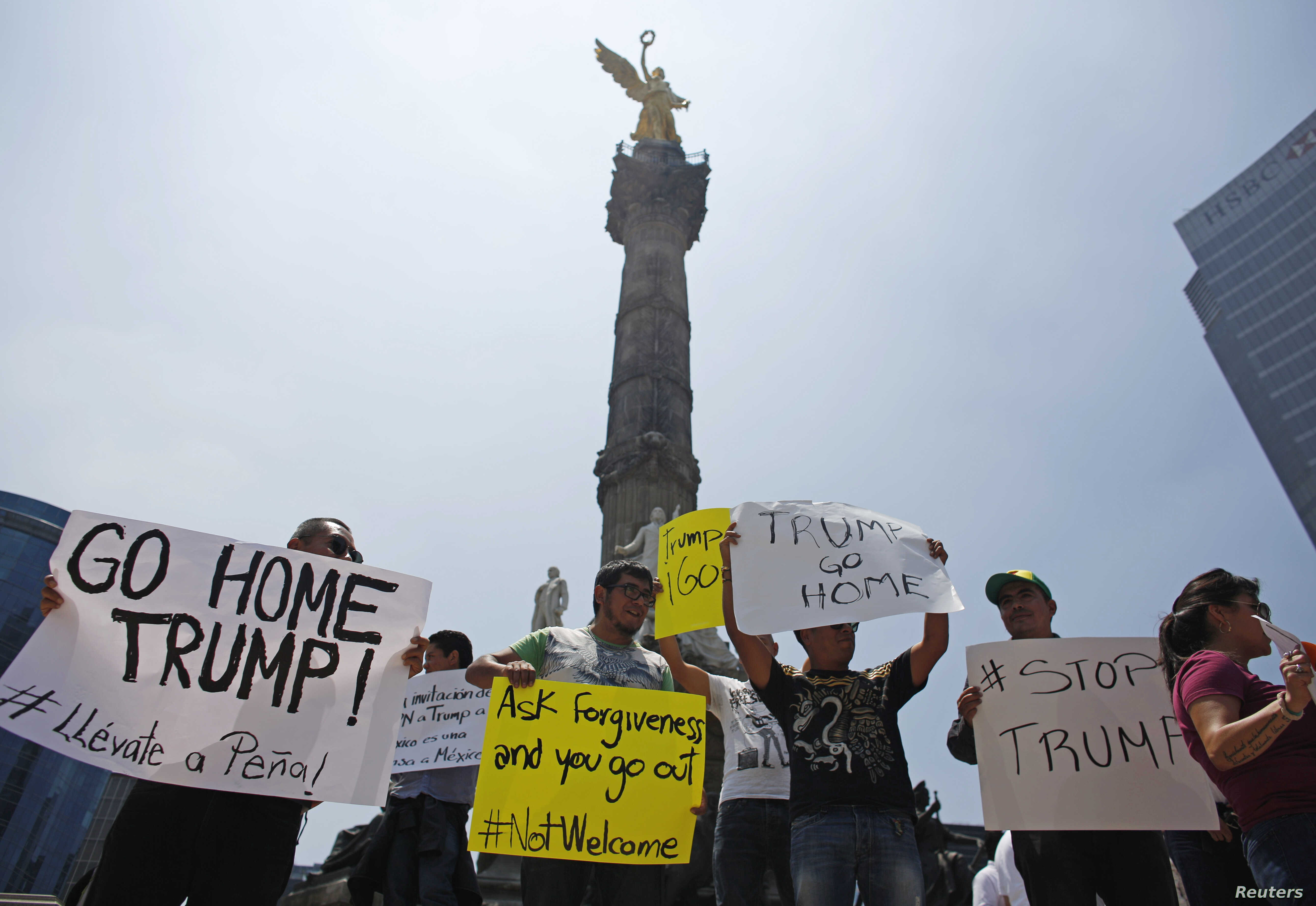 Demonstrators hold placards during a protest against the visit of U.S. Republican presidential candidate Donald Trump at the Angel of Independence monument in Mexico City, Mexico, Aug. 31, 2016.