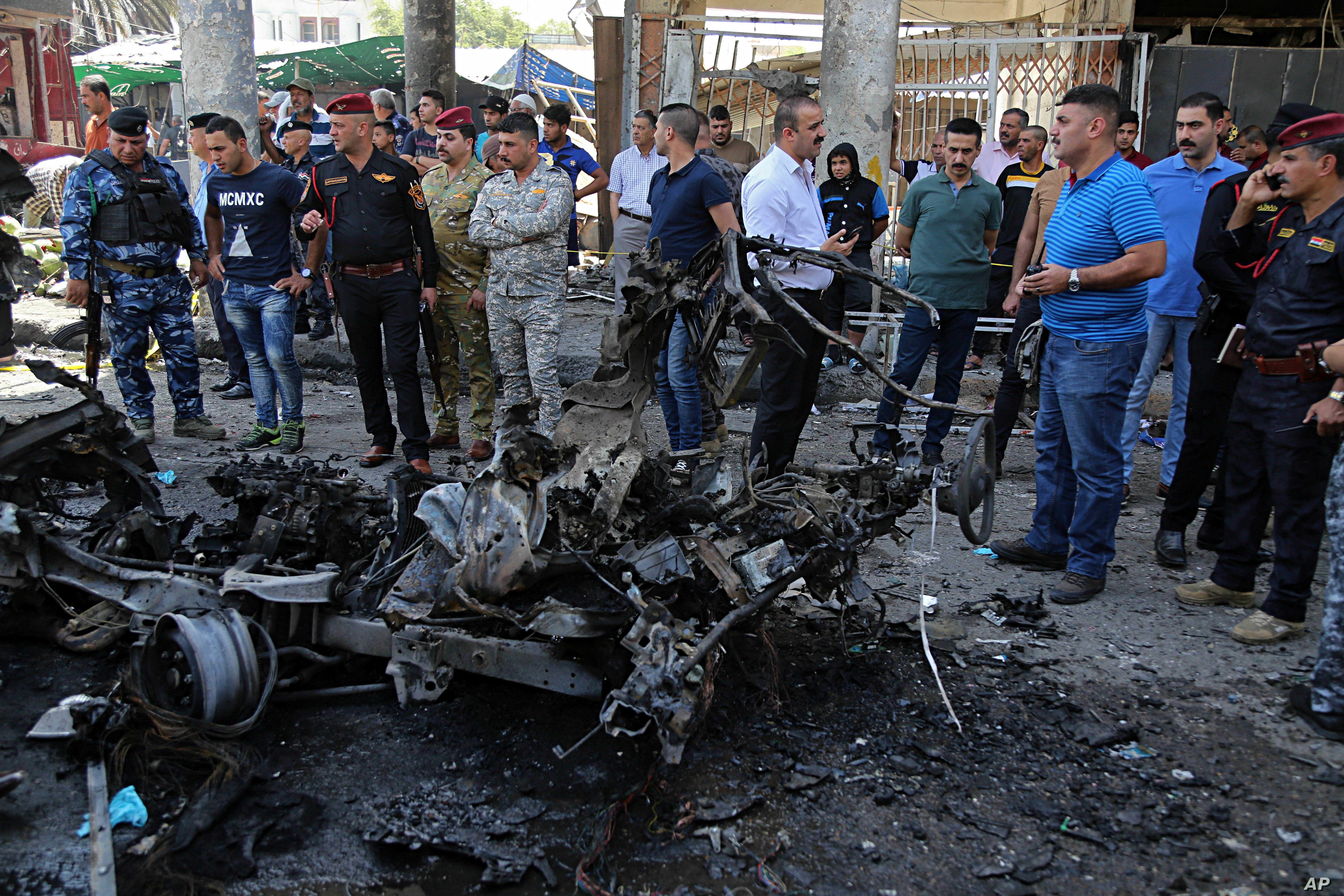 Iraqi security forces and civilians inspect the site of a deadly car bomb explosion, in Baghdad, Iraq, May 30, 2017.