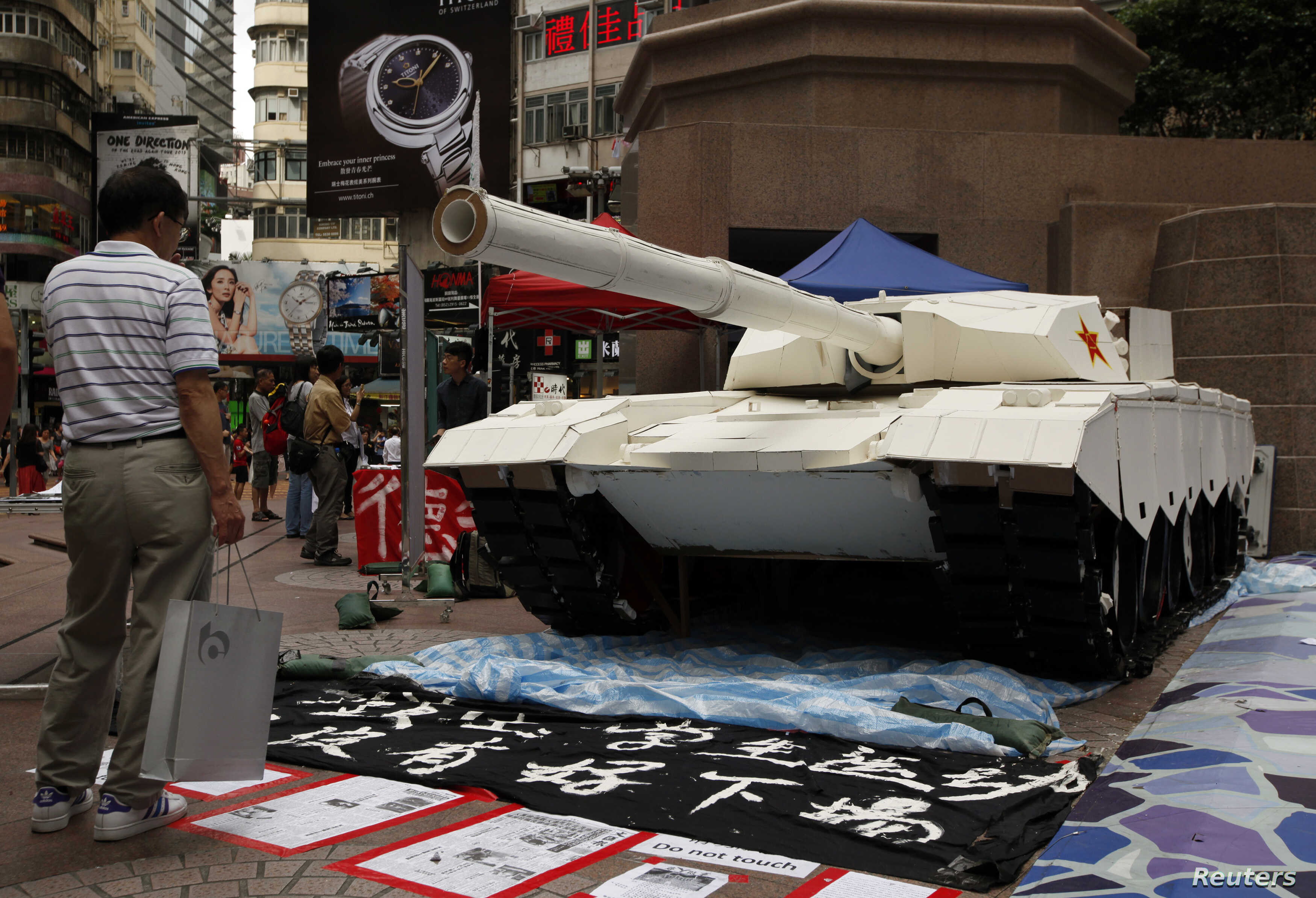 A shopper in Hong Kong stands in front of a model tank made by university students to remember the crackdown in Tiananmen Square, June 3, 2014.
