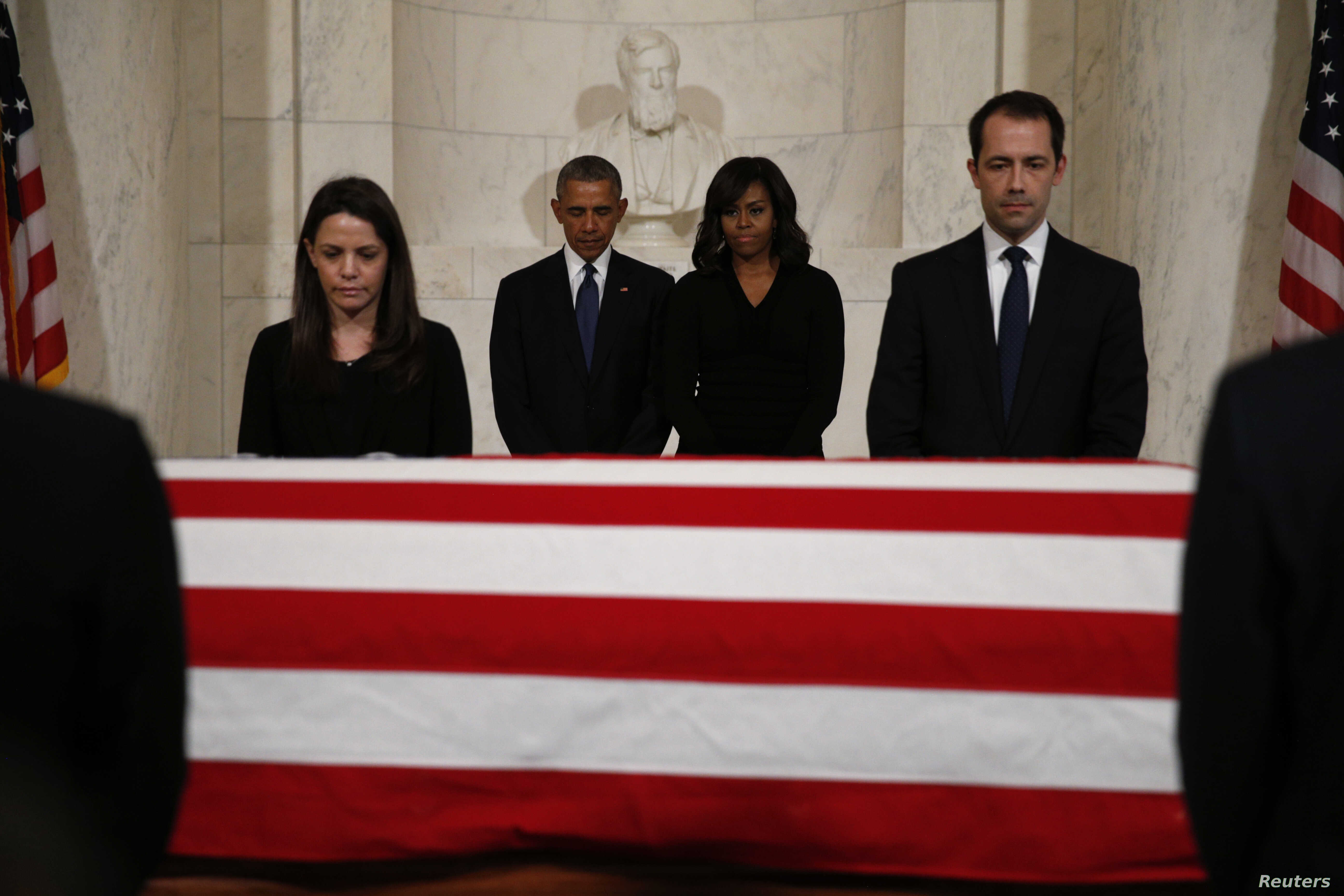 President Barack Obama, second from left, and first lady Michelle Obama, second from right, pay their respects at the casket of Supreme Court Justice Antonin Scalia in the Supreme Court's Great Hall in Washington, Feb. 19, 2016.
