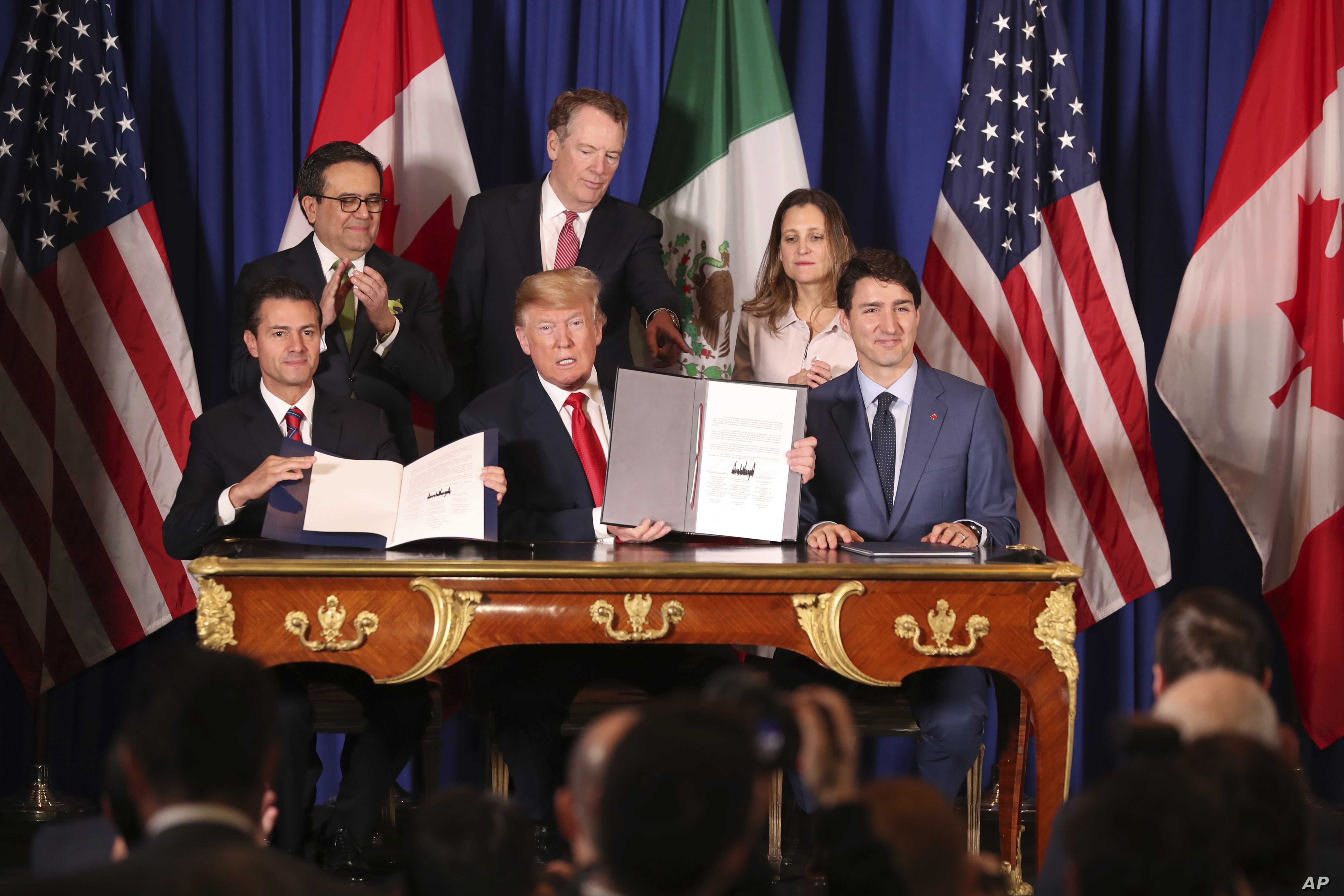 President Donald Trump, center, sits between Canada's Prime Minister Justin Trudeau, right, and Mexico's President Enrique Pena Nieto after they signed a new U.S.-Mexico-Canada Agreement that is replacing the NAFTA trade deal.
