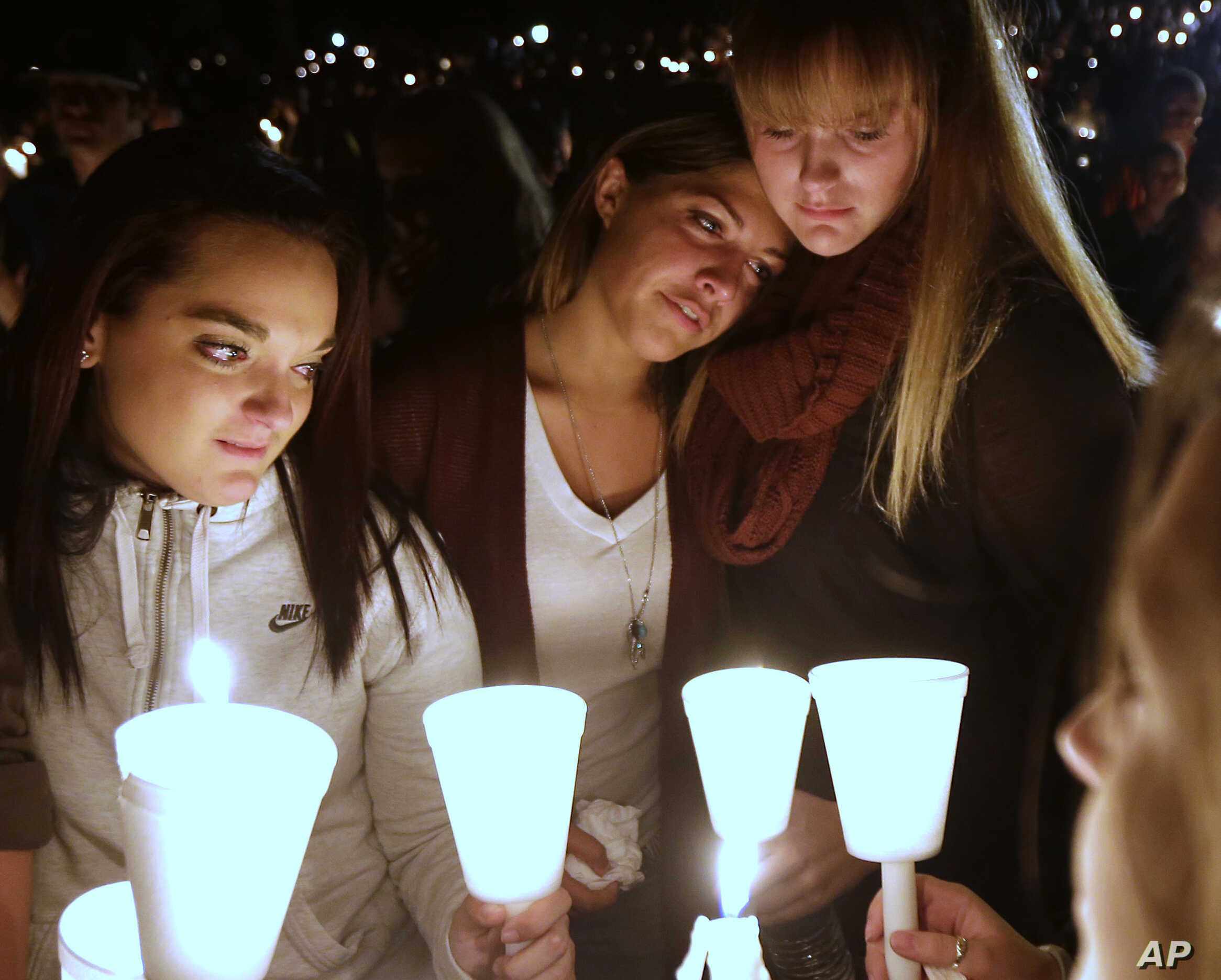 Umpqua Community College students Nicole Zamarripa, left, Kristen Sterner, center and Carrissa Welding, right, join others at Stewart Park, in Roseburg, Ore., for a candlelight vigil for those killed during a fatal shooting at the school, Oct. 1, 201...