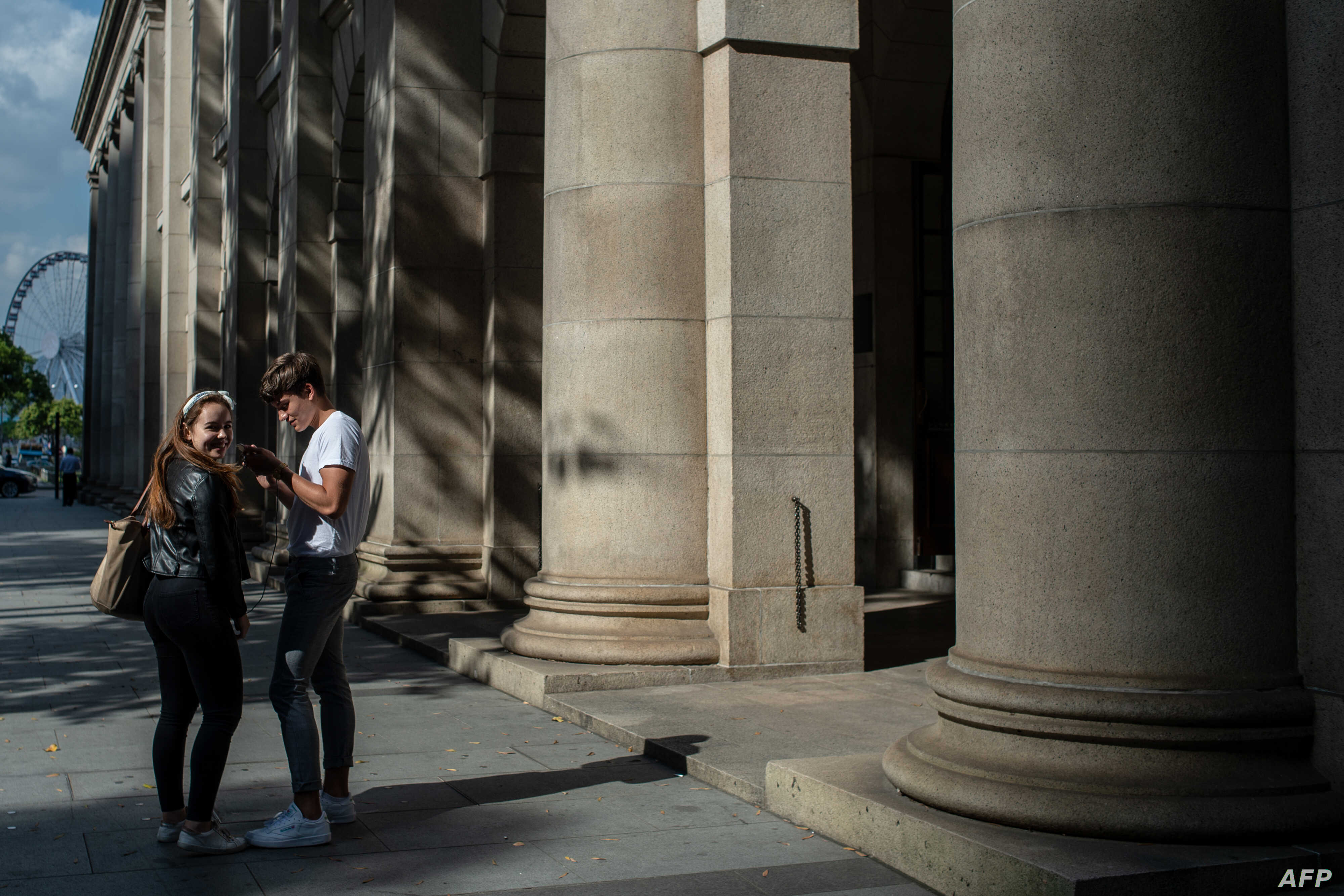 A couple stands in front of the Court of Final Appeal building in Hong Kong, April 10, 2018.