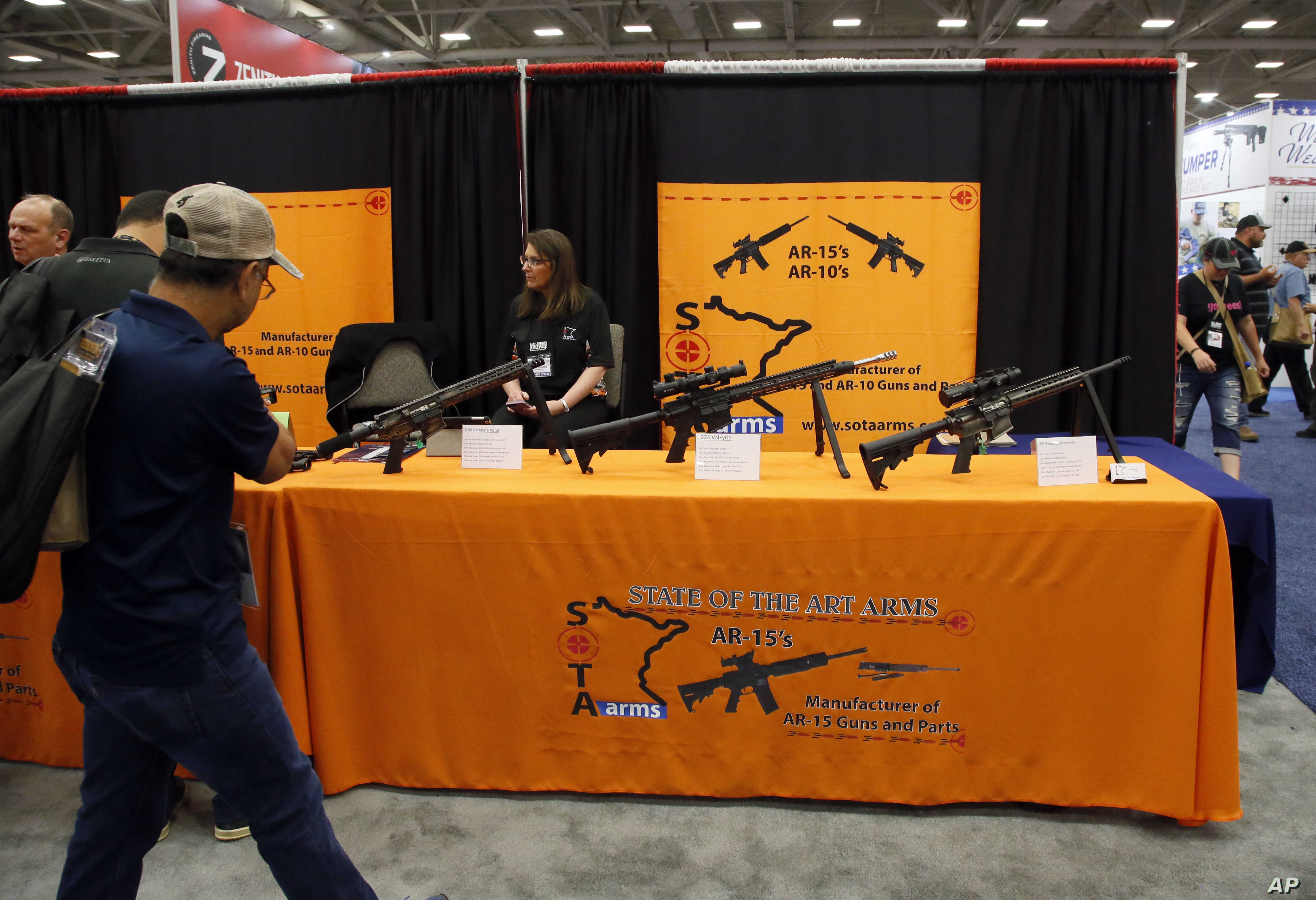 Attendees walk by a display of AR-15's and AR-10's at the National Rifle Association convention in Dallas, May 4, 2018.