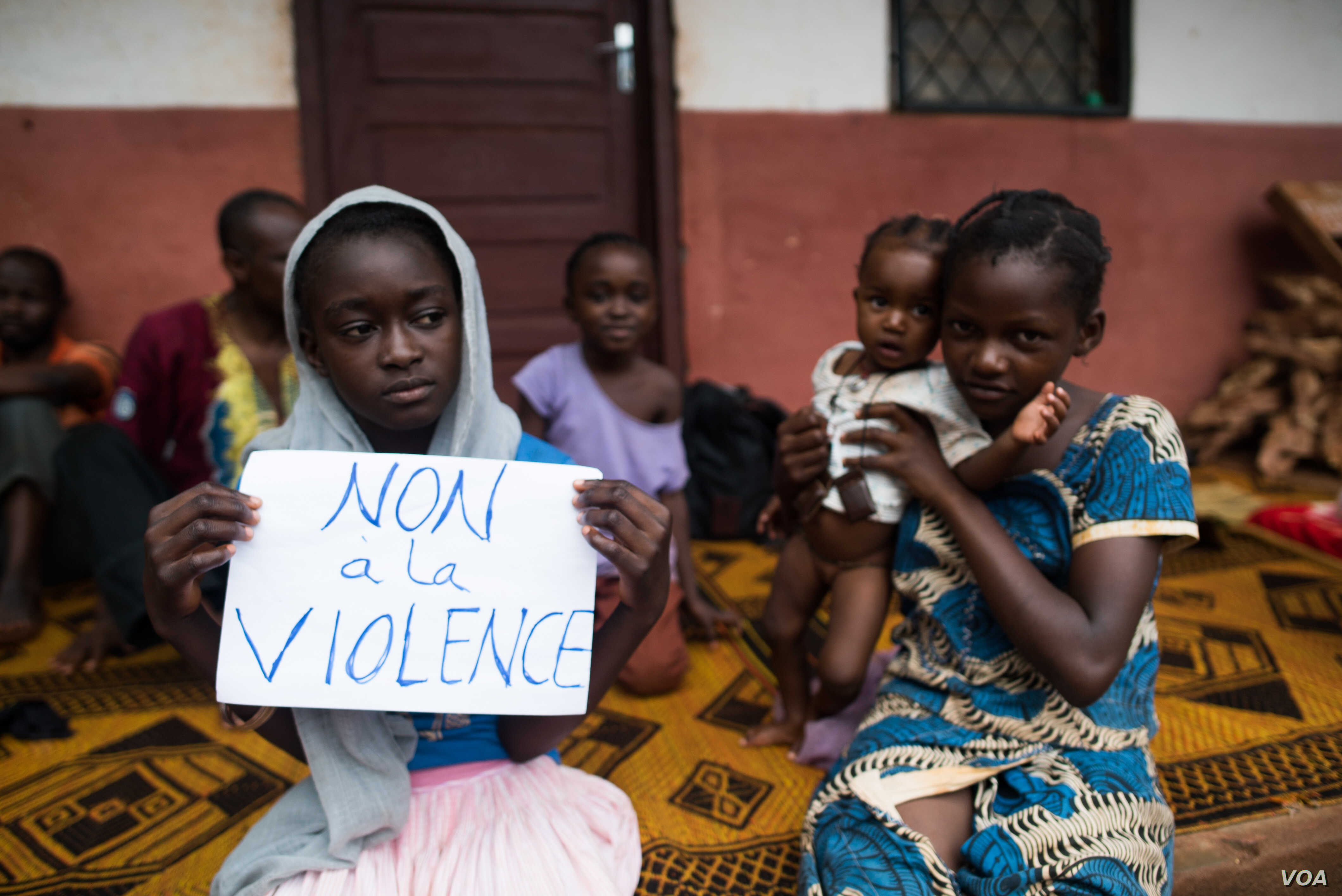 """A young displaced Muslim girl holds a sign saying """"No to Violence"""" at a displaced persons site, the Catholic church in Bangassou, Central African Republic."""